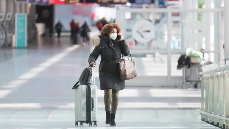 Una pasajera lleva una máscara facial mientras camina por el Aeropuerto Internacional Pierre Elliot Trudeau de Montreal.