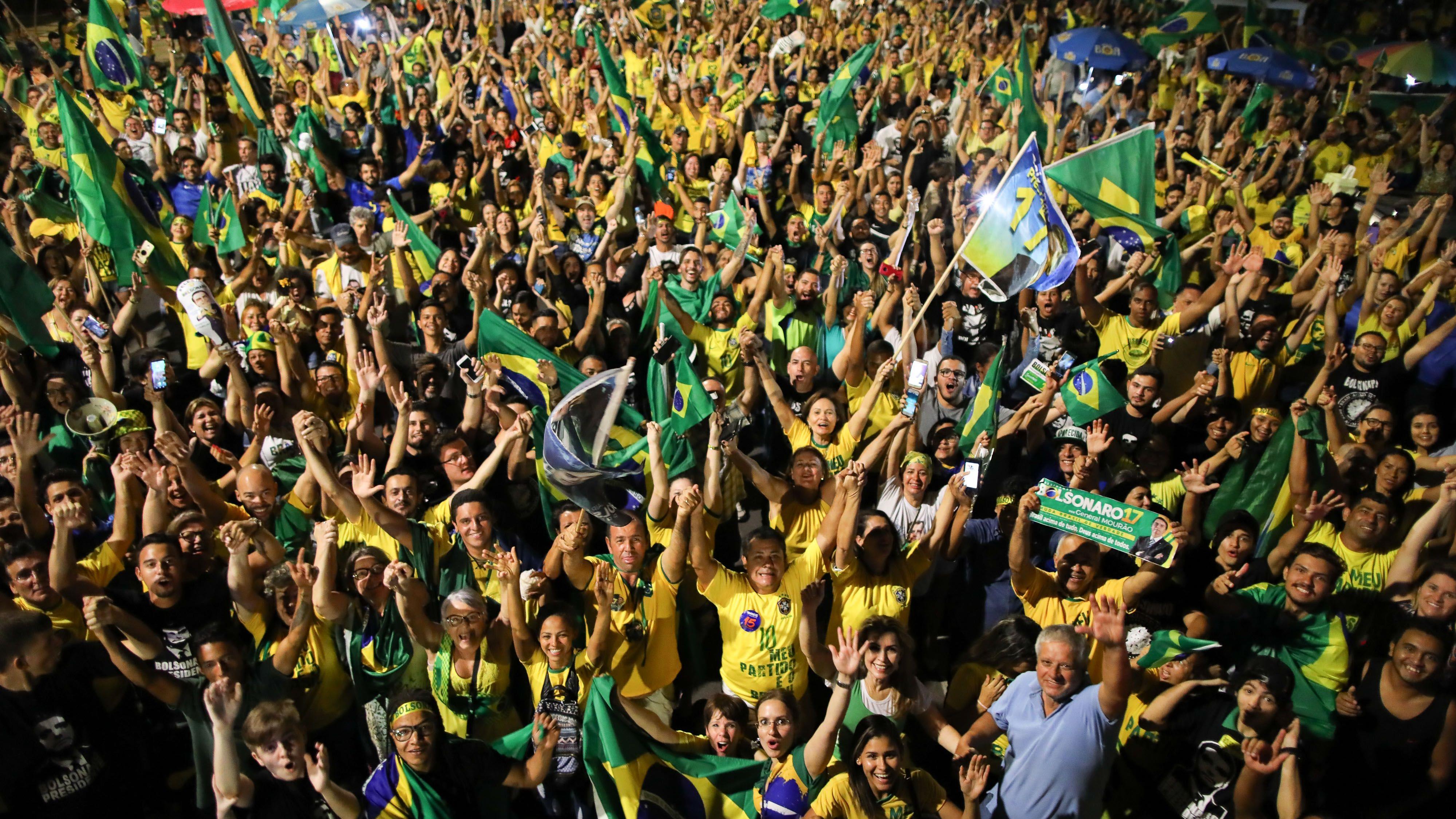 Des partisans de Jair Bolsonaro fêtent la victoire de leur candidat en agitant des drapeaux du Brésil, à Brasilia, le 28 octobre 2018.