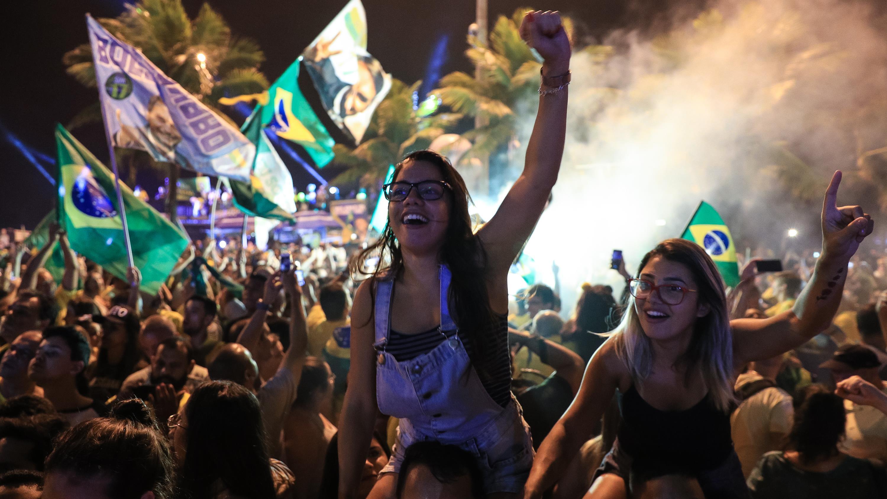 Deux jeunes admiratrices de Jair Bolsonaro célèbrent la victoire de leur candidat, le 28 octobre 2018 à Rio de Janeiro, en soulevant leur poing dans les airs au milieu de la foule.