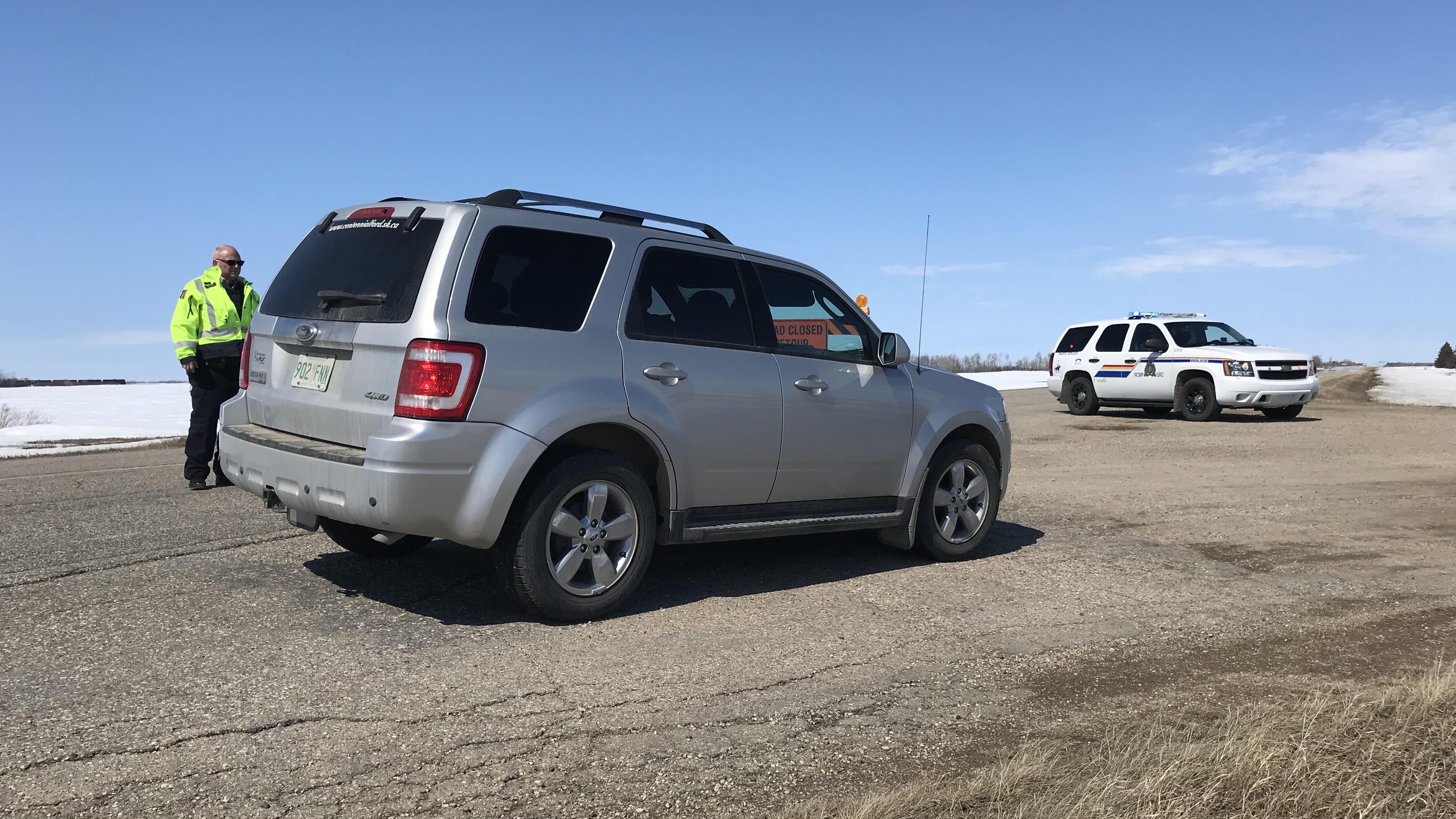 En avant-plan, un VUS gris est stationné au milieu de la route devant une barricade. En arrière-plan, un VUS de la GRC est également stationné sur la route. Un agent de la GRC est debout derrière le VUS banalisé.