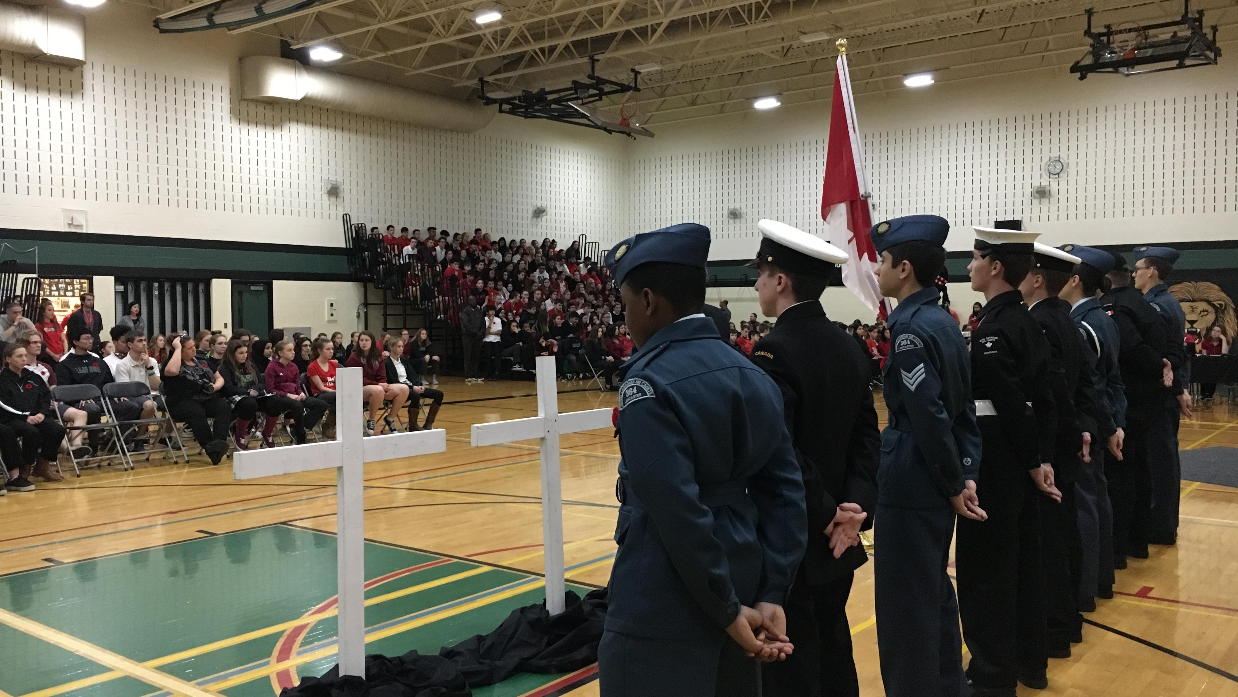 Des officiers de réserve et des cadets font face à une foule de jeunes.