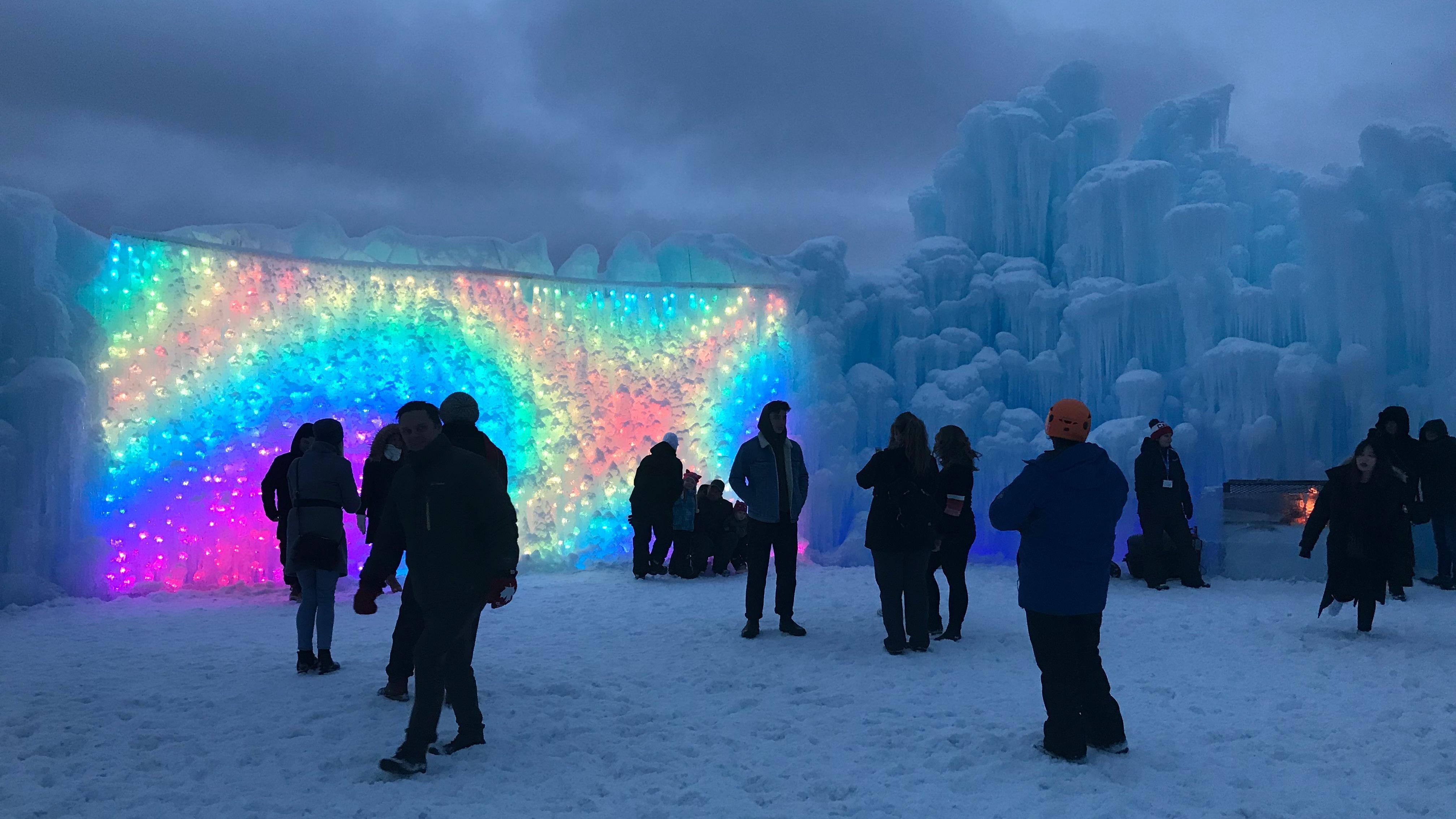 Des lumières multicolores illuminent un mur de glace.
