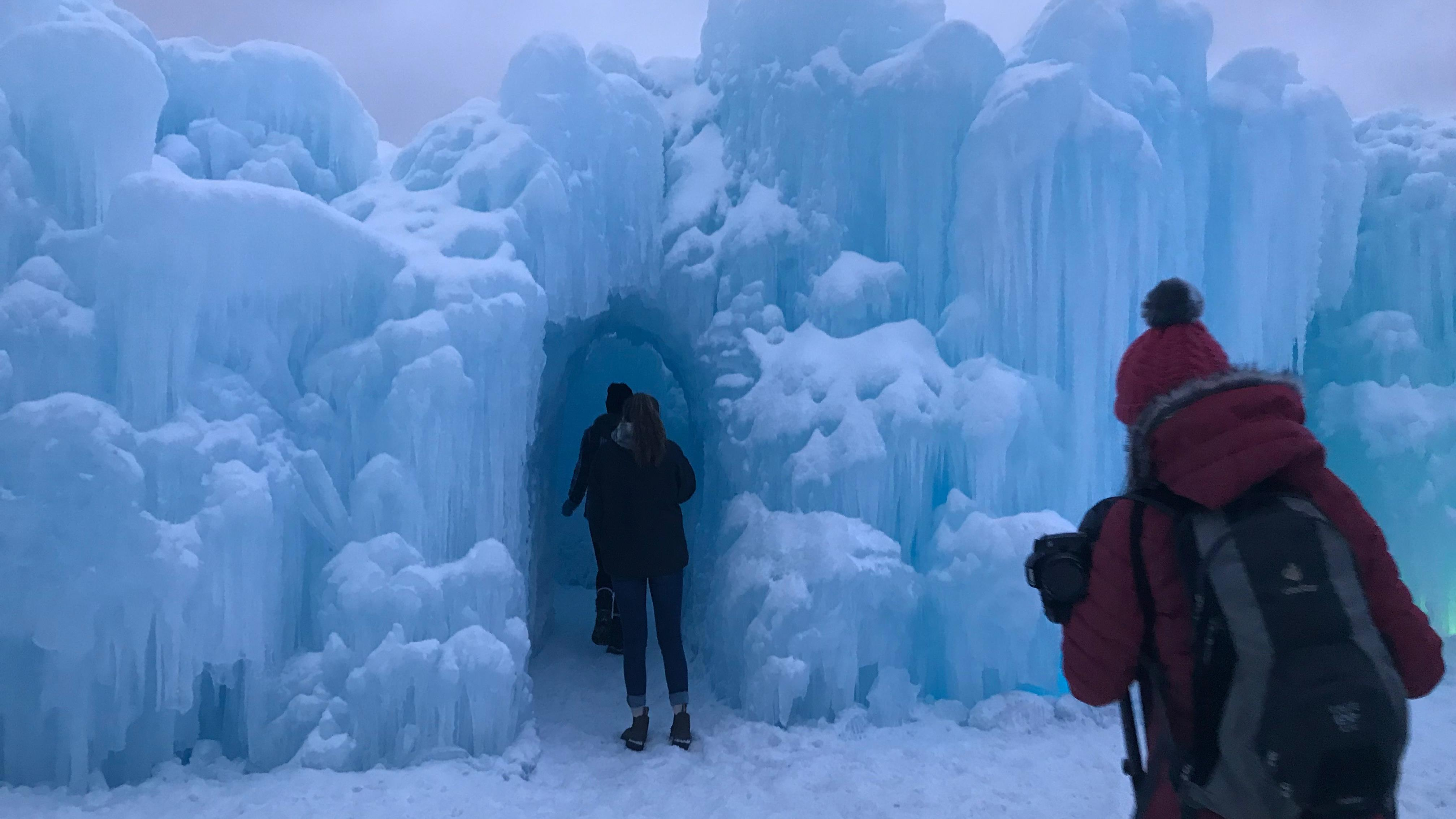 Des visiteurs traversent un tunnel de glace.
