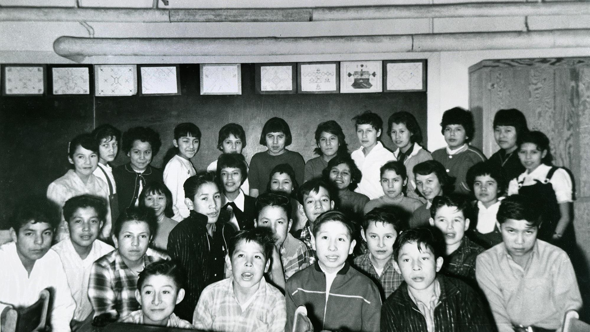 Des élèves, garçons et filles, posent pour la photo dans une classe. Ils sont debout, derrière une rangée de pupitres, et des dessins (motifs autochtones?) sont accrochés au mur derrière le groupe.