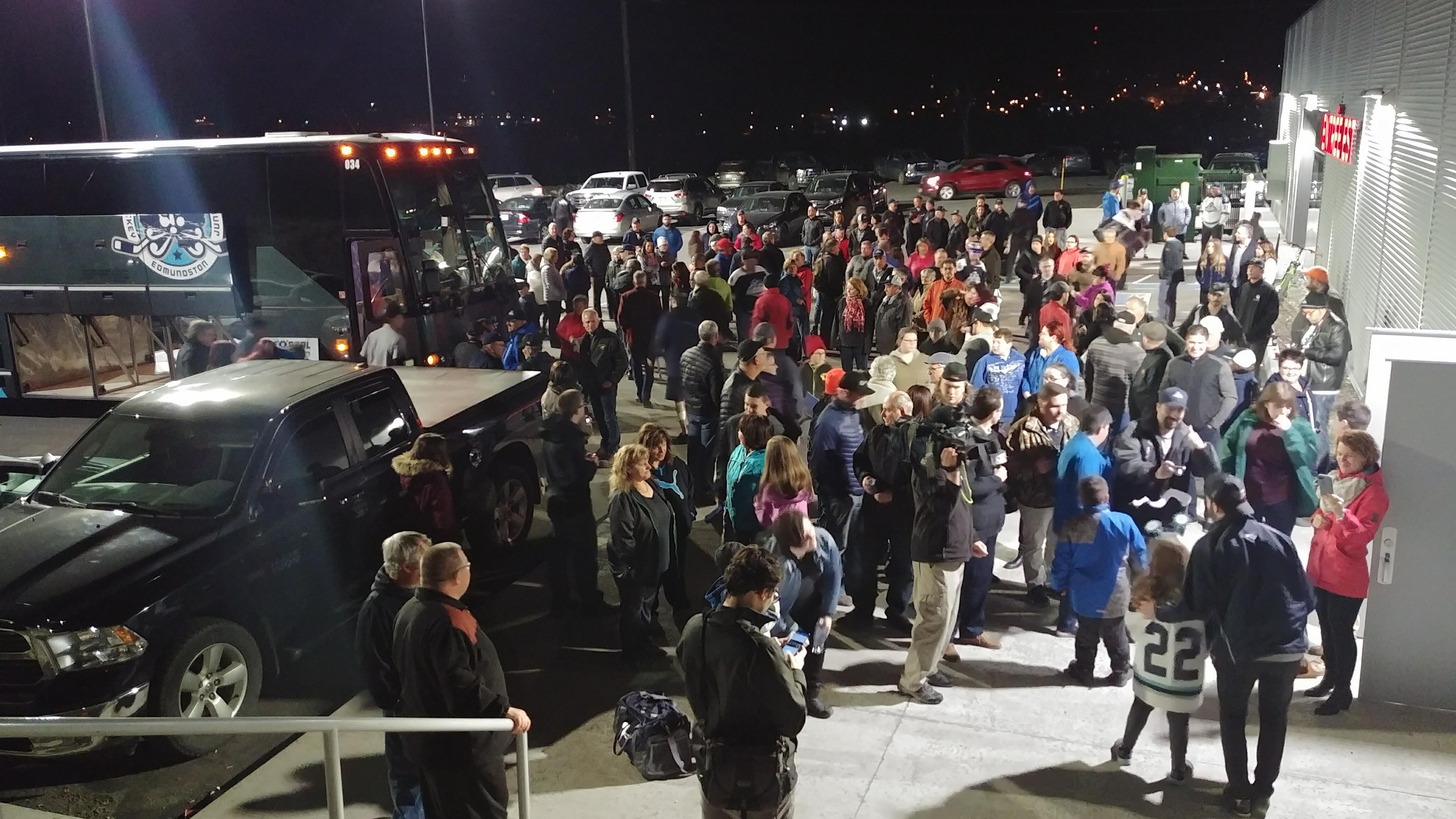 Une foule entoure les joueurs qui descendent d'un autobus.