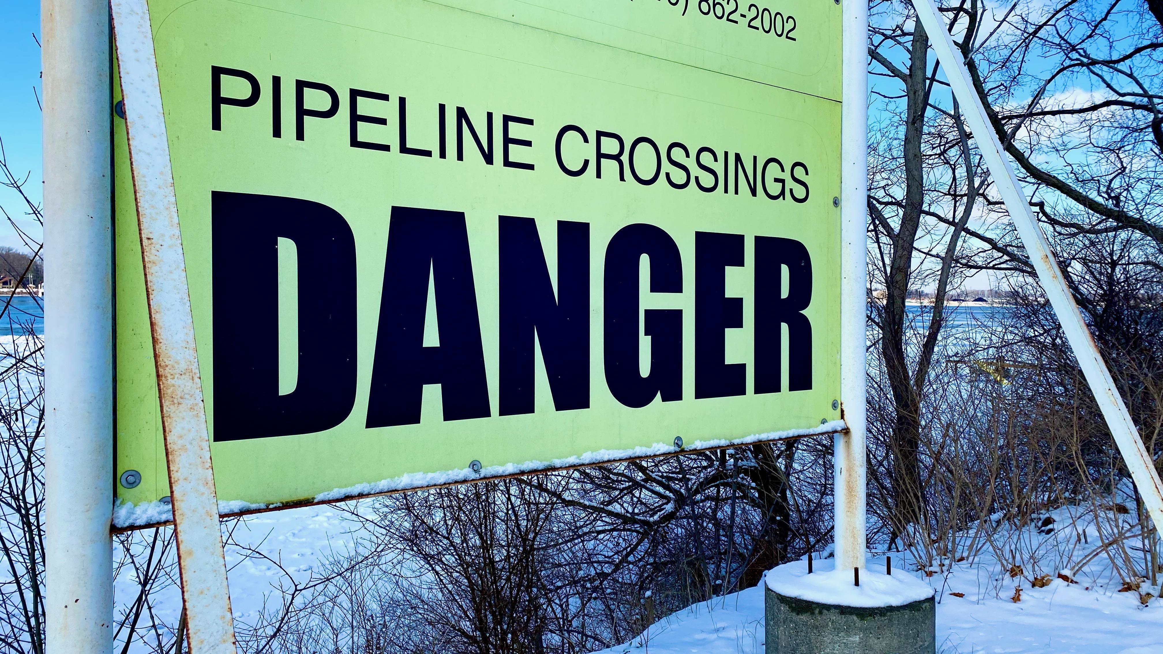 Un afiche indica que un oleoducto está pasando bajo el agua.
