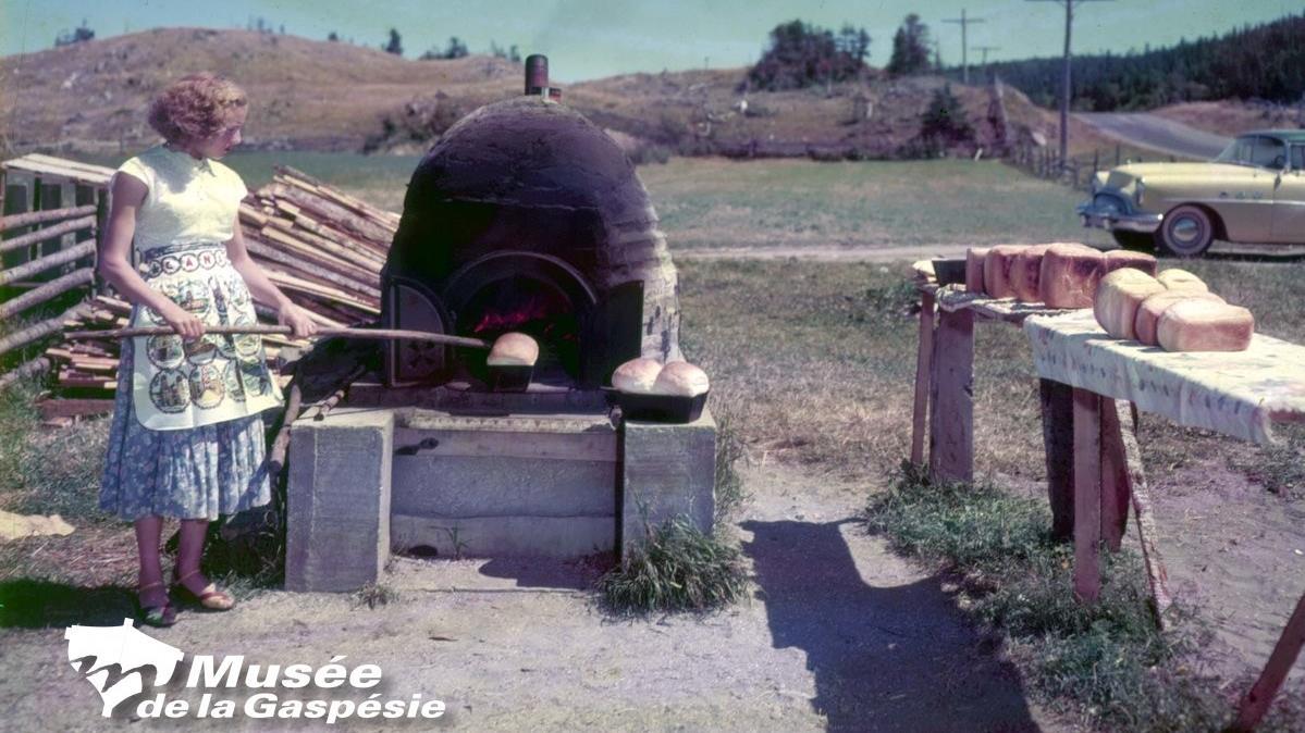 Négatif représentant une jeune femme sortant un pain d'un four à pain vers 1950.