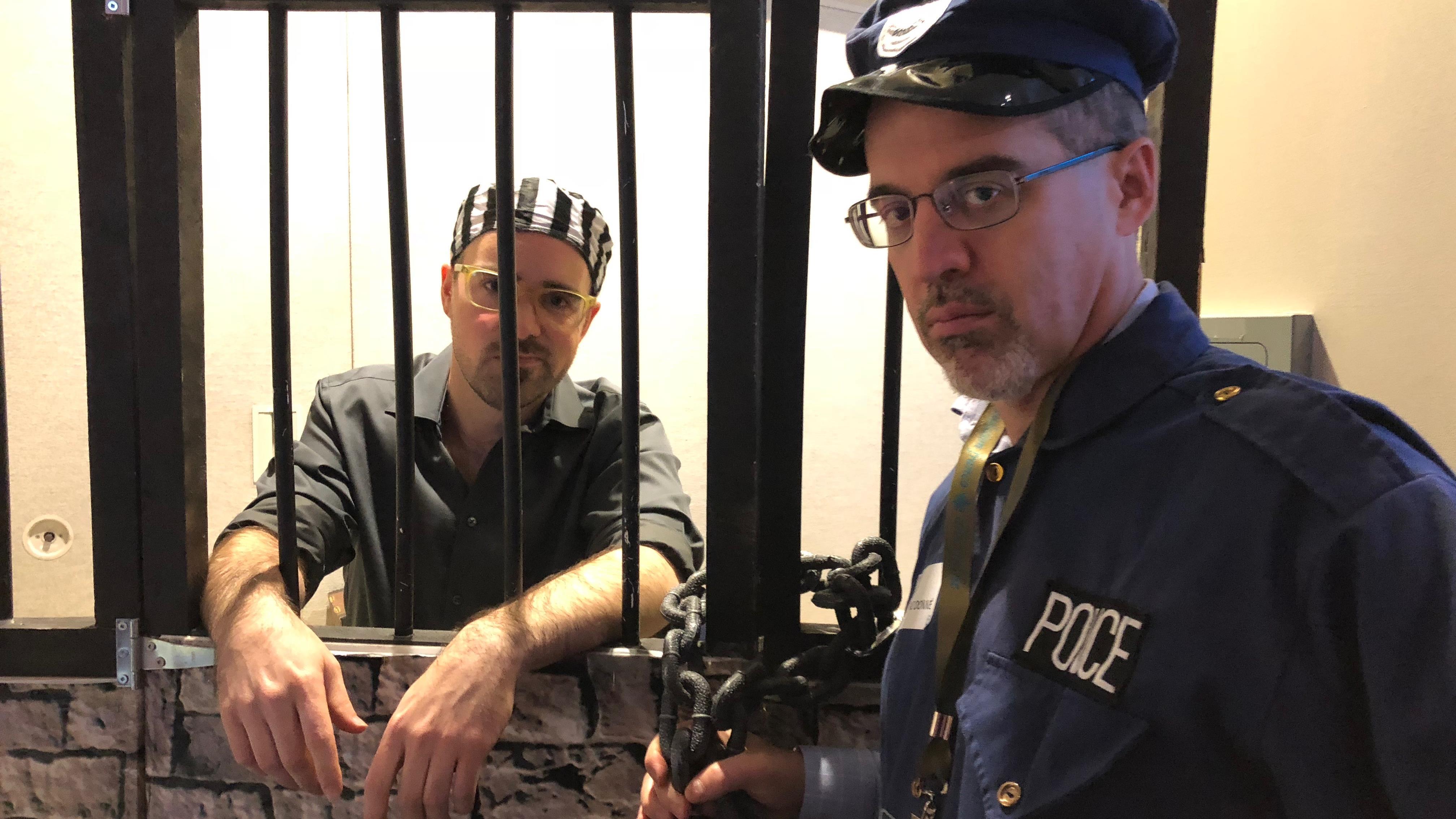 Raphaël Freynet habillé en prisonnier derrière les barreaux, et Étienne Alary costumé en policier.