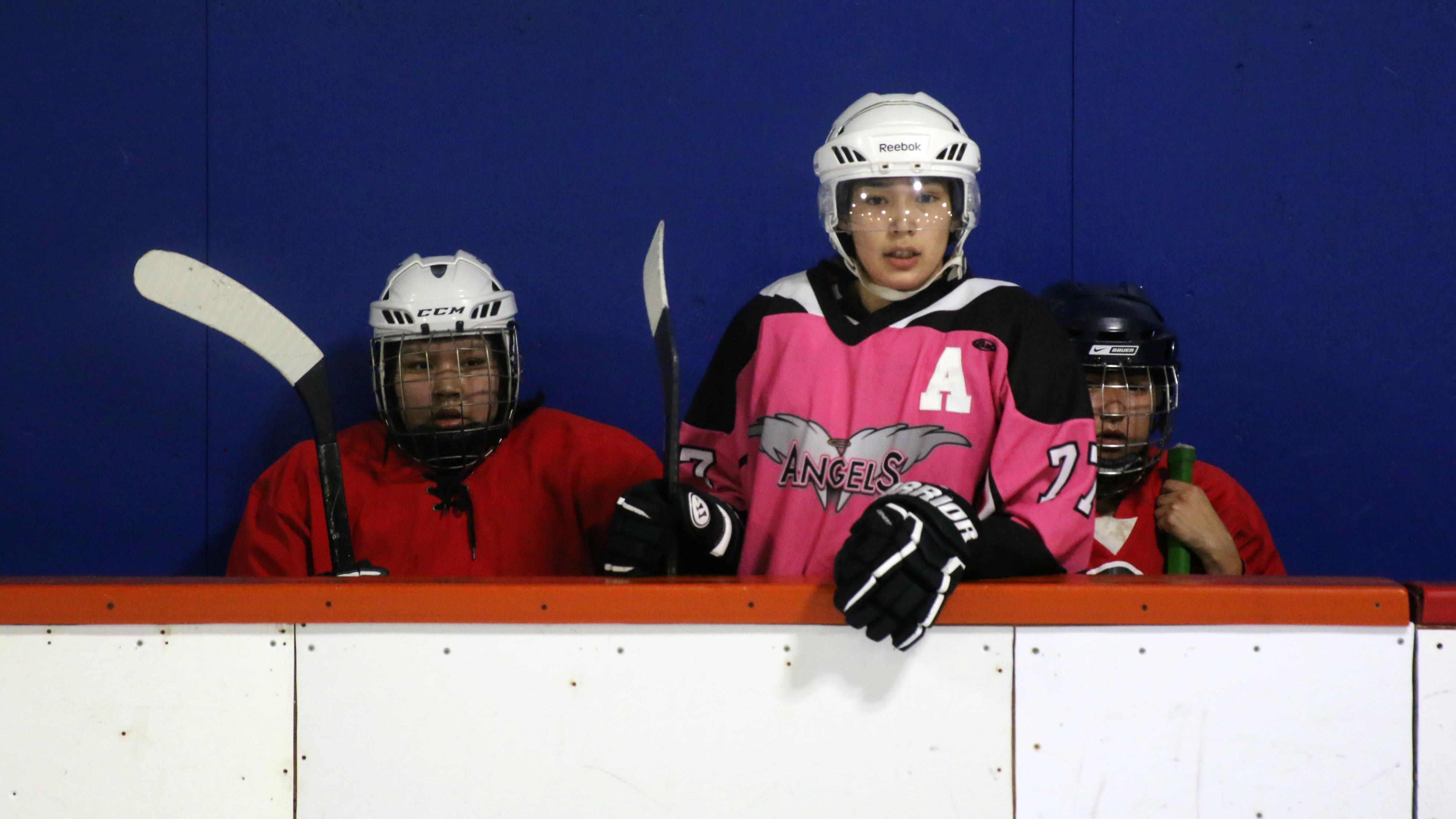 Des joueuses de hockey observent un match du banc de leur équipe, lors d'un tournoi de hockey autochtone à Val-d'Or.