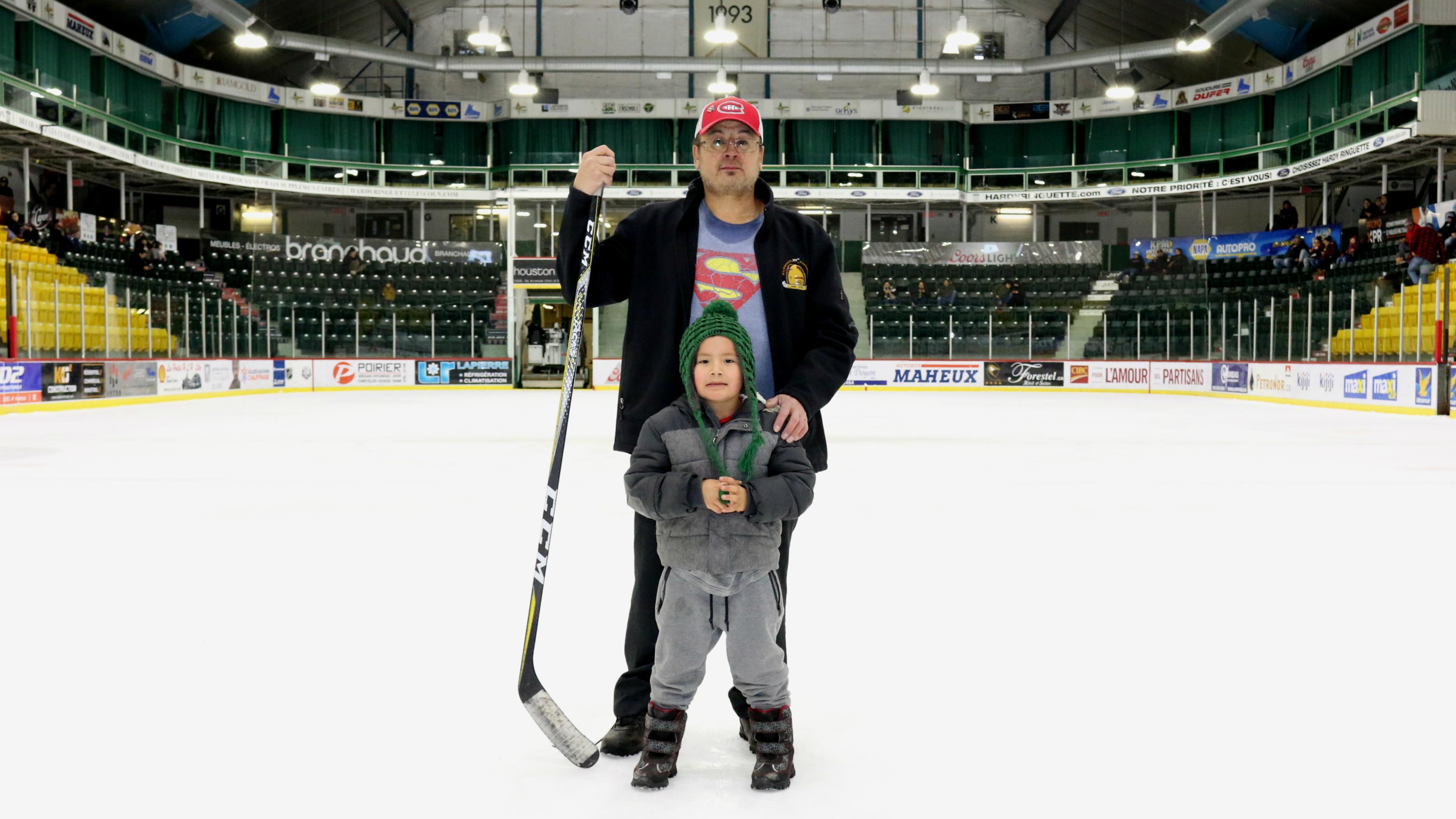 Charles Hester pose avec son fils cadet au milieu de la glace du Centre Air Creebec de Val-d'Or.