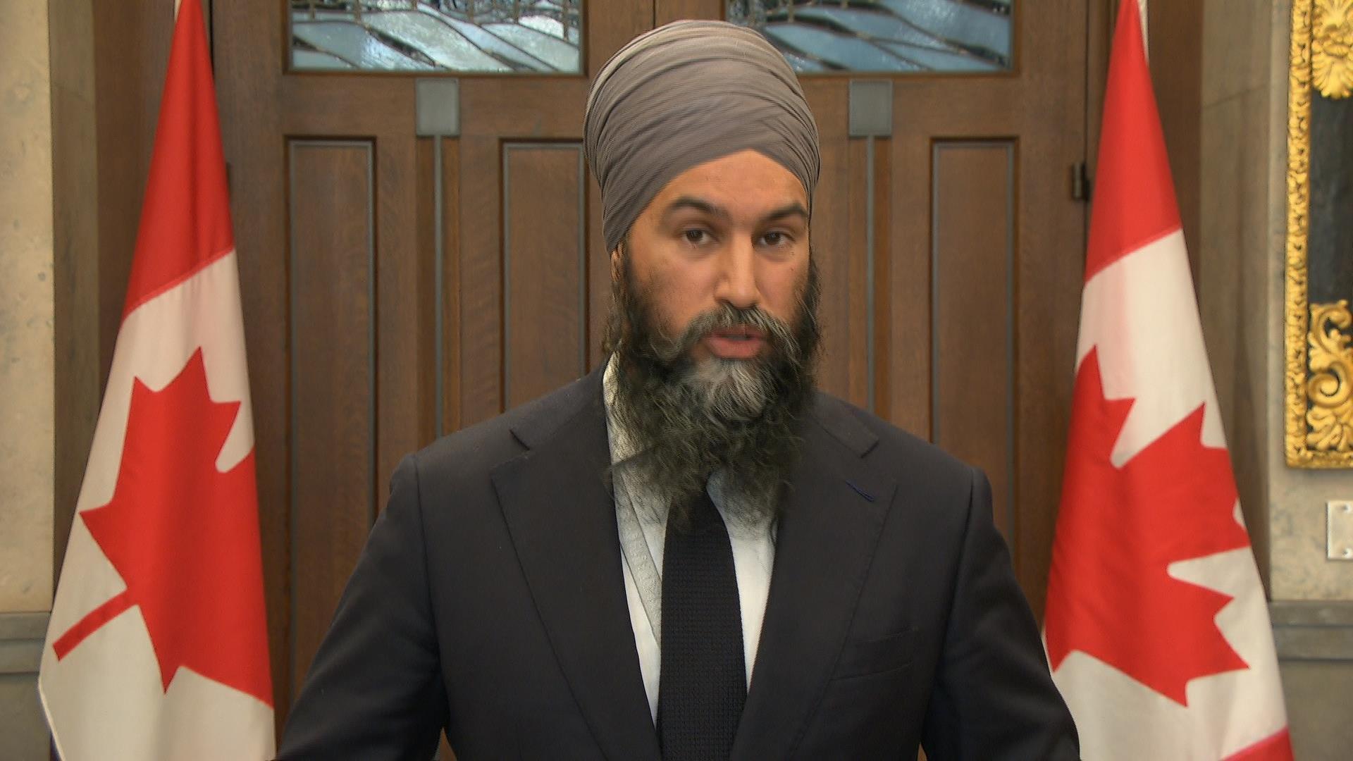 Jagmeet Singh hace declaraciones en Ottawa con el trasfondo de dos banderas canadienses.