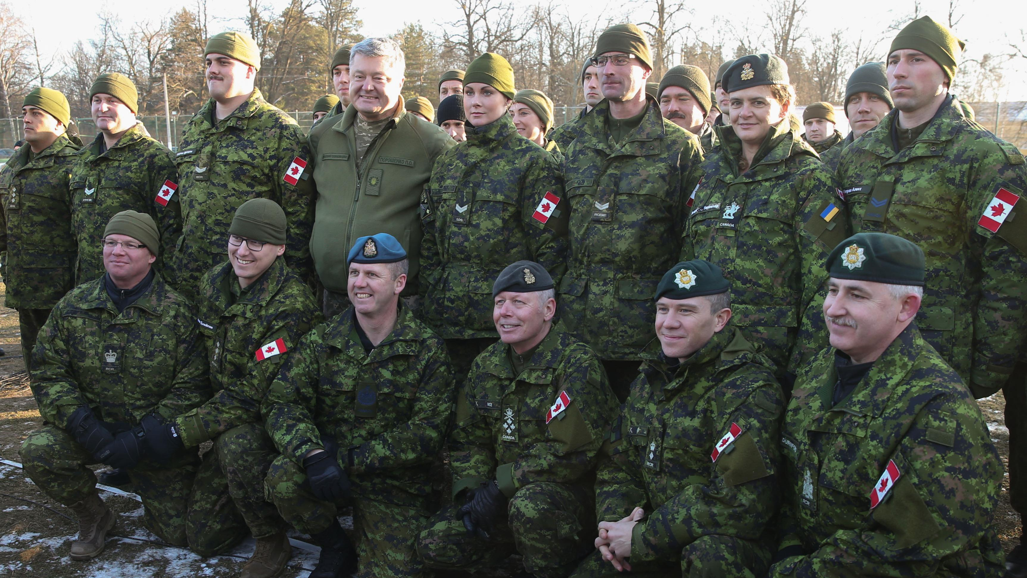 Canadian Gov. Gen. Julie Payette (second right, top row) and Ukrainian President Petro Poroshenko pose for a photo with Canadian soldiers at the International Peacekeeping and Security Centre, on Thursday, Jan. 18, 2018.