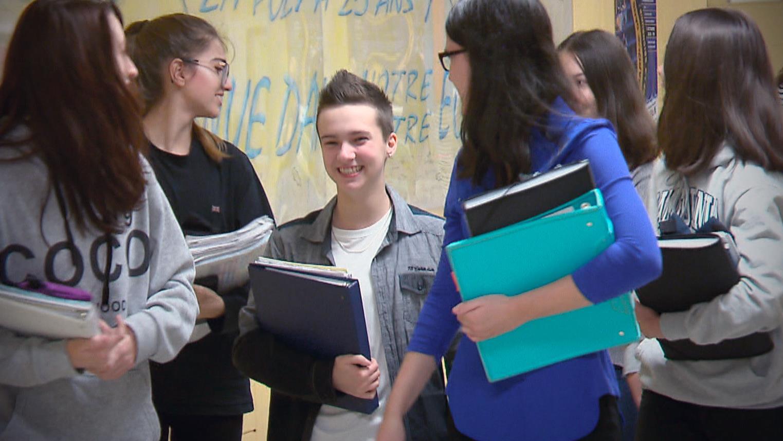 Loukas dans un corridor de l'école, entouré de ses amies