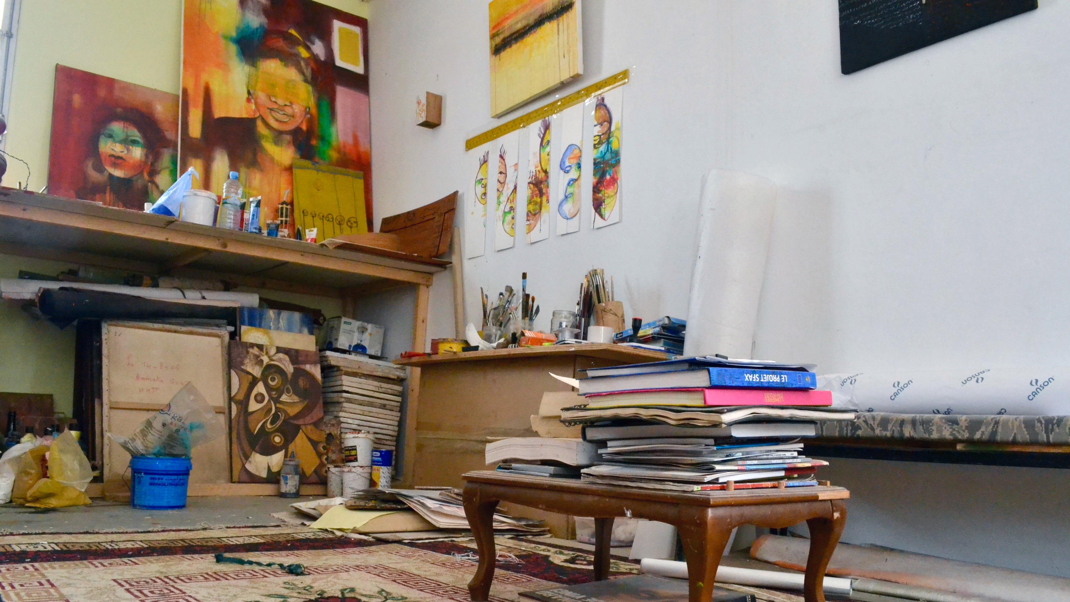 Des toiles inachevées représentant des visages de femmes dans l'atelier d'Amy Sow