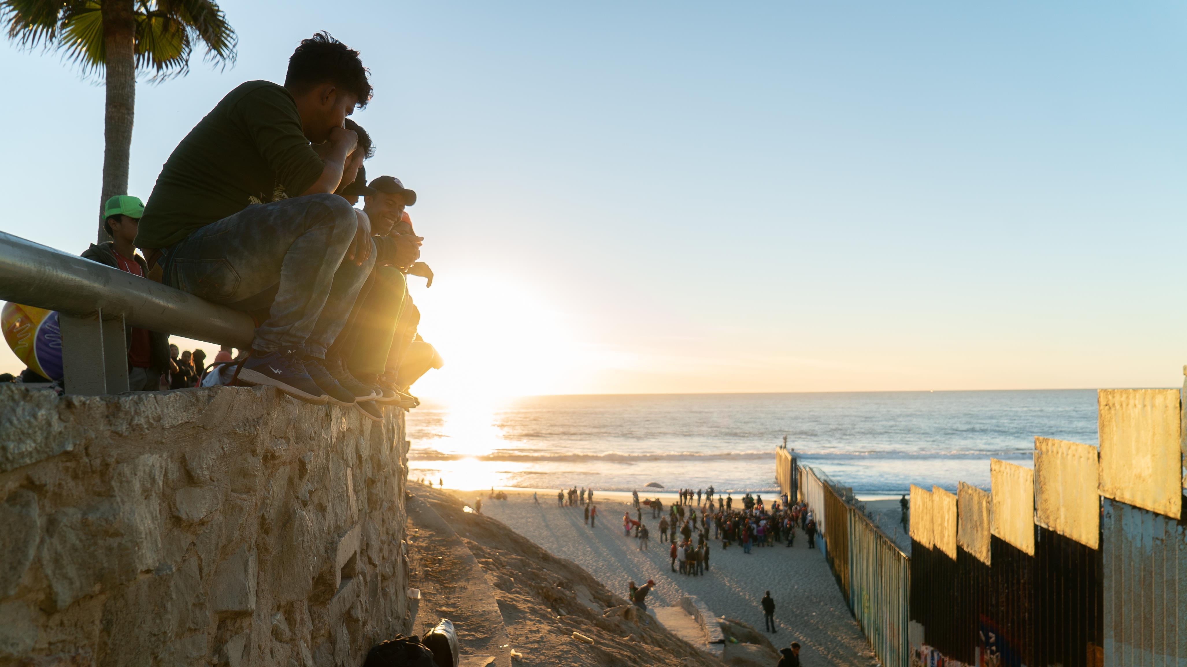 De jeunes hommes perchés sur un parapet regardent la mer et le mur qui les séparent des États-Unis.
