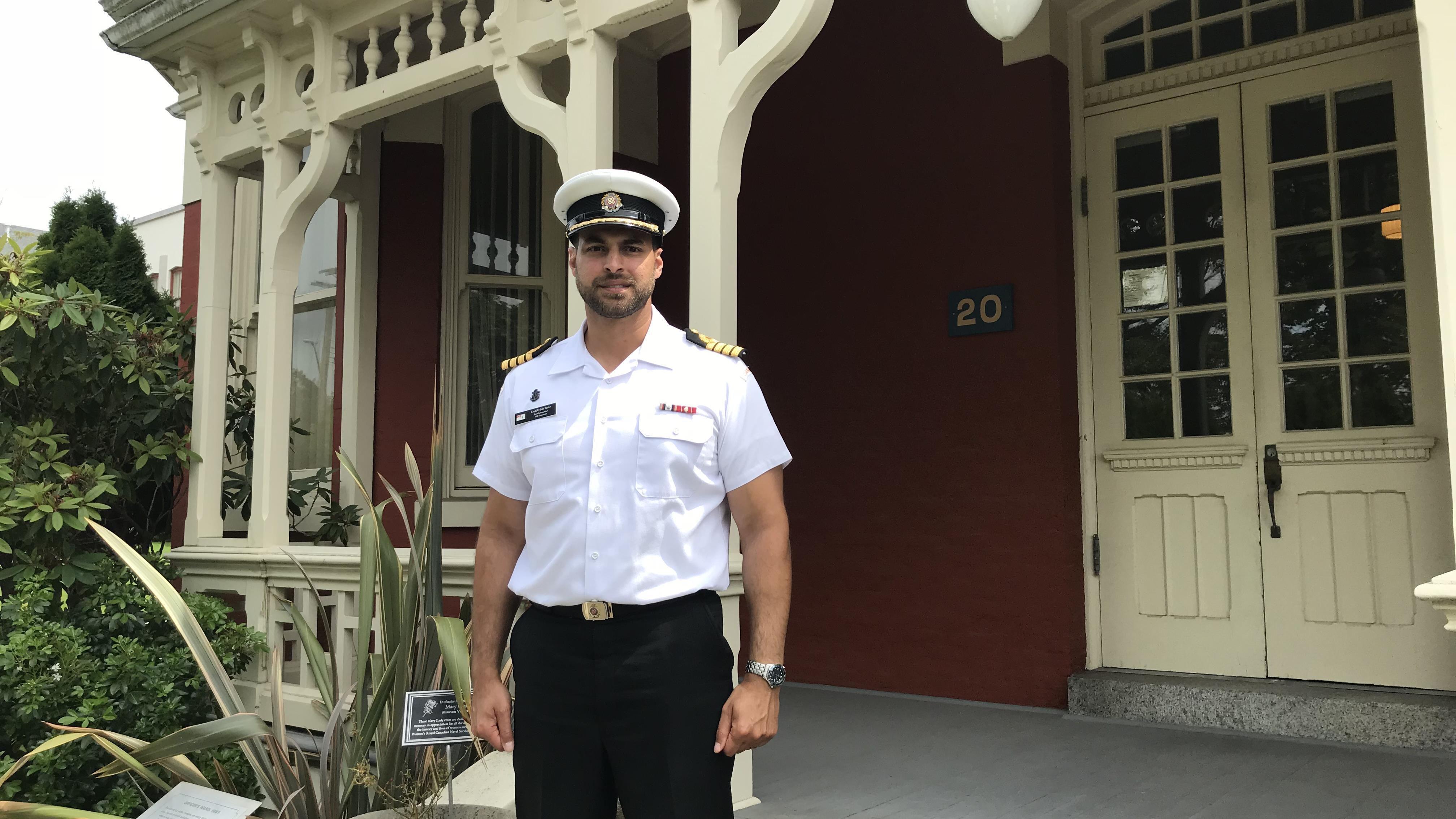 Le capitaine de vaisseau Sam Sader devant la petite école rouge.