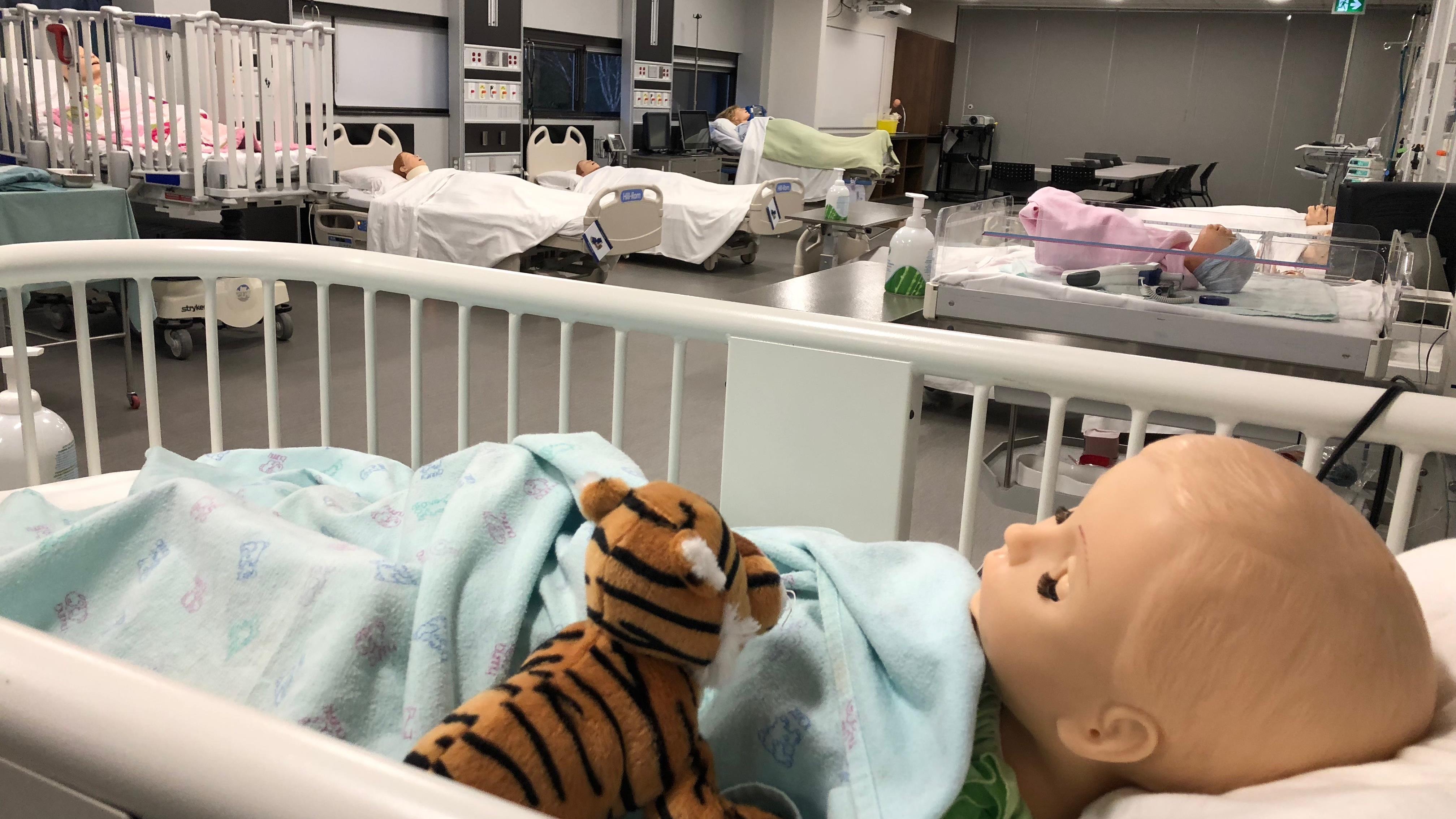 Des mannequins d'enfants sont couchés dans des lits d'hôpital dans une salle de classe.