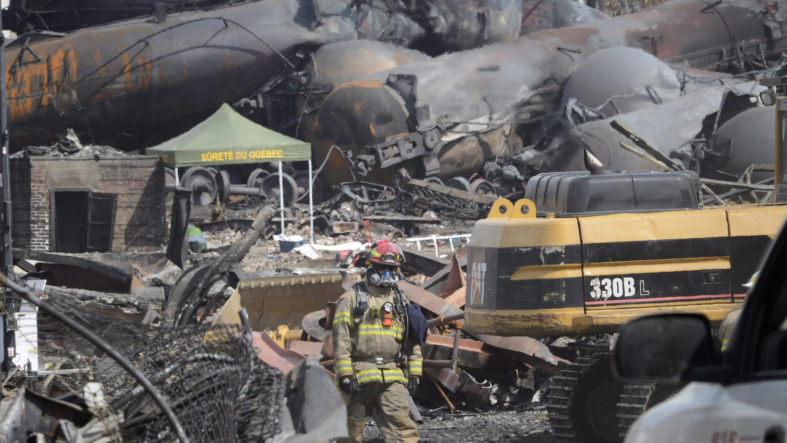 A firefighter inspects the damage left by the derailment and explosion of the runaway train in Lac-Megantic.