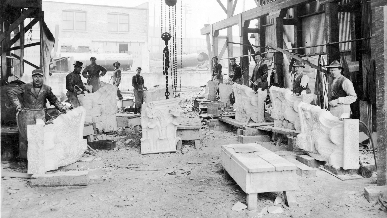Des travailleurs tiennent des moulures qui serviront à la construction du bâtiment du crédit foncier franco-canadien.