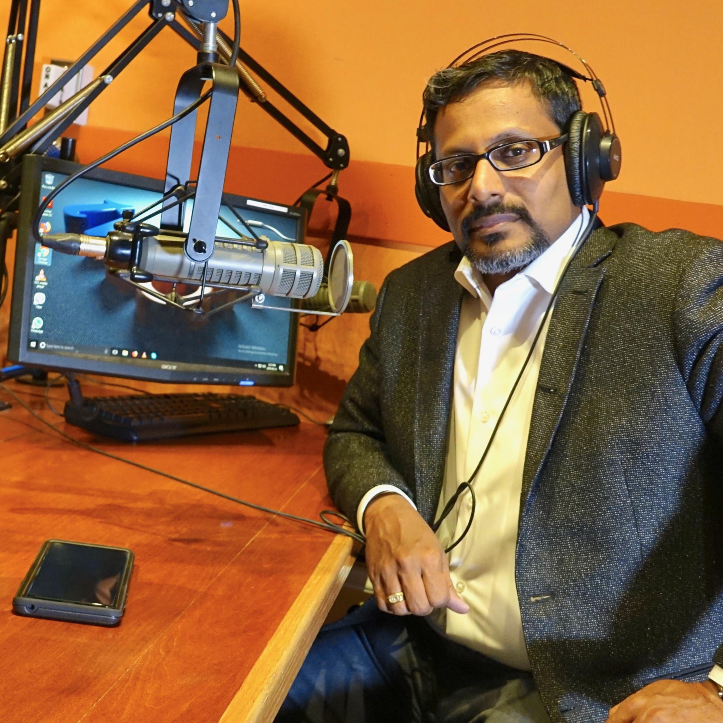 EL señor Pillai est sentado en un estudio de radio