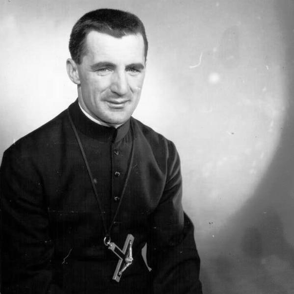 Raynald Couture pose avec un crucifix autour du cou.