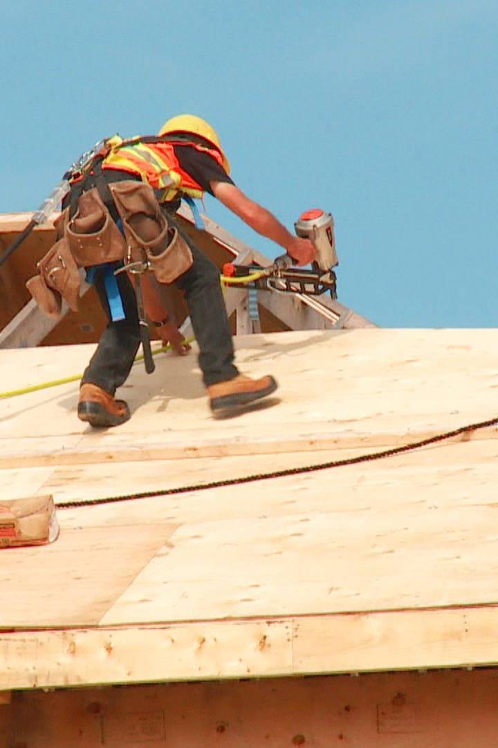 Trabajadores de la construcción trabajan en un techo.