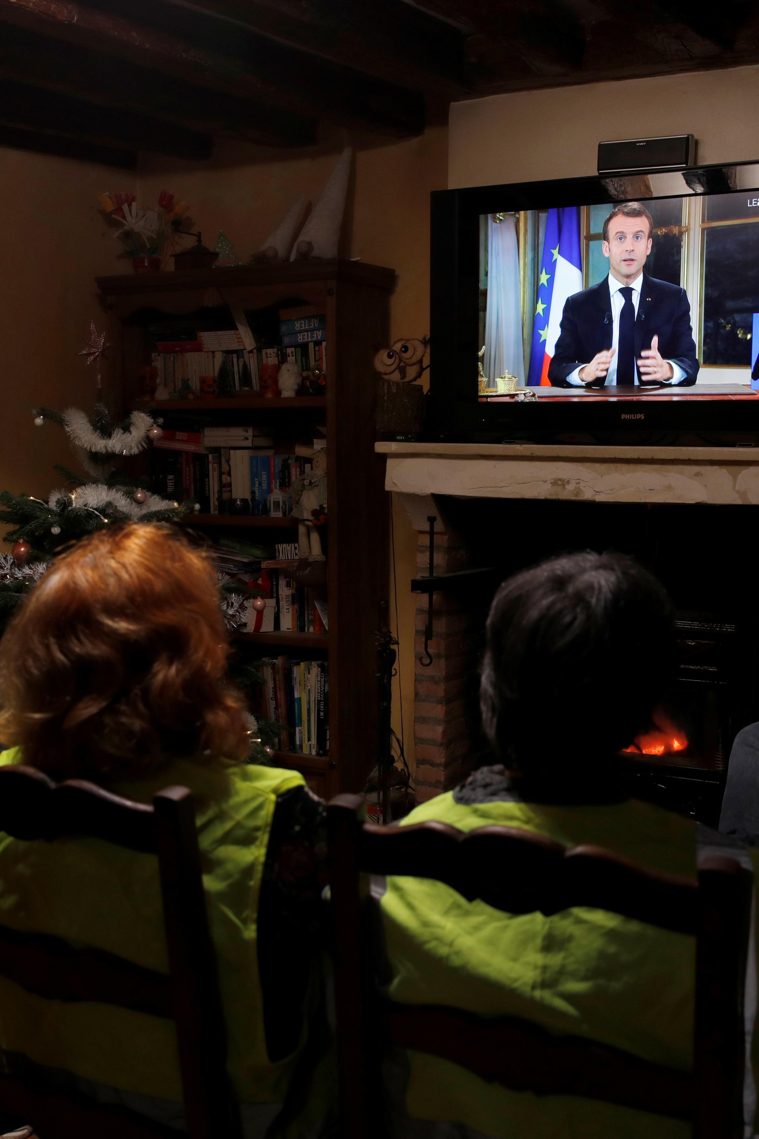 Des gilets jaunes regardent le discours du président Emmanuel Macron, à Gaillon, en France, le 10 décembre 2018.