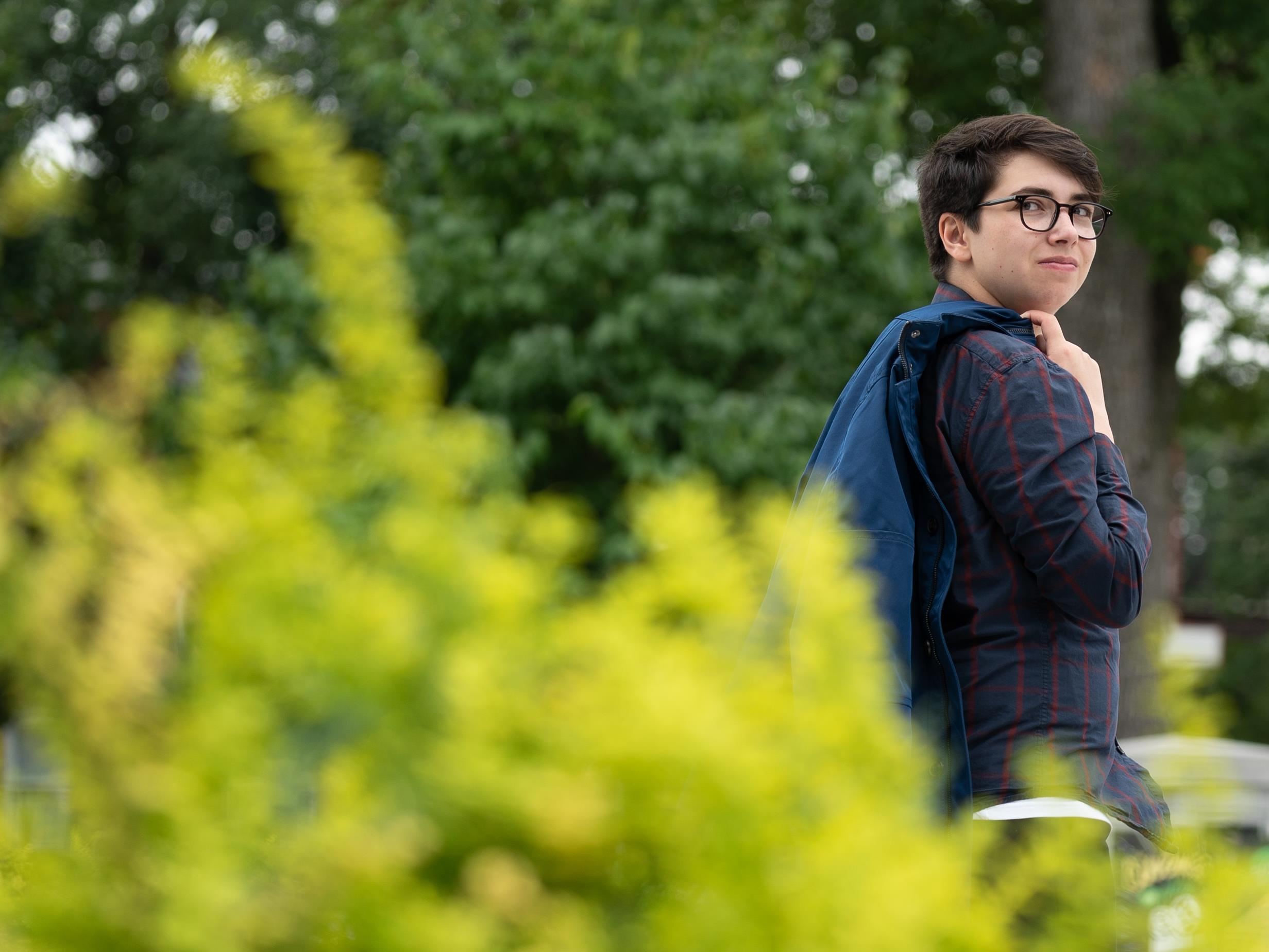 On voit Adam, debout, de profil, dans un parc. Il porte son manteau sur l'épaule.