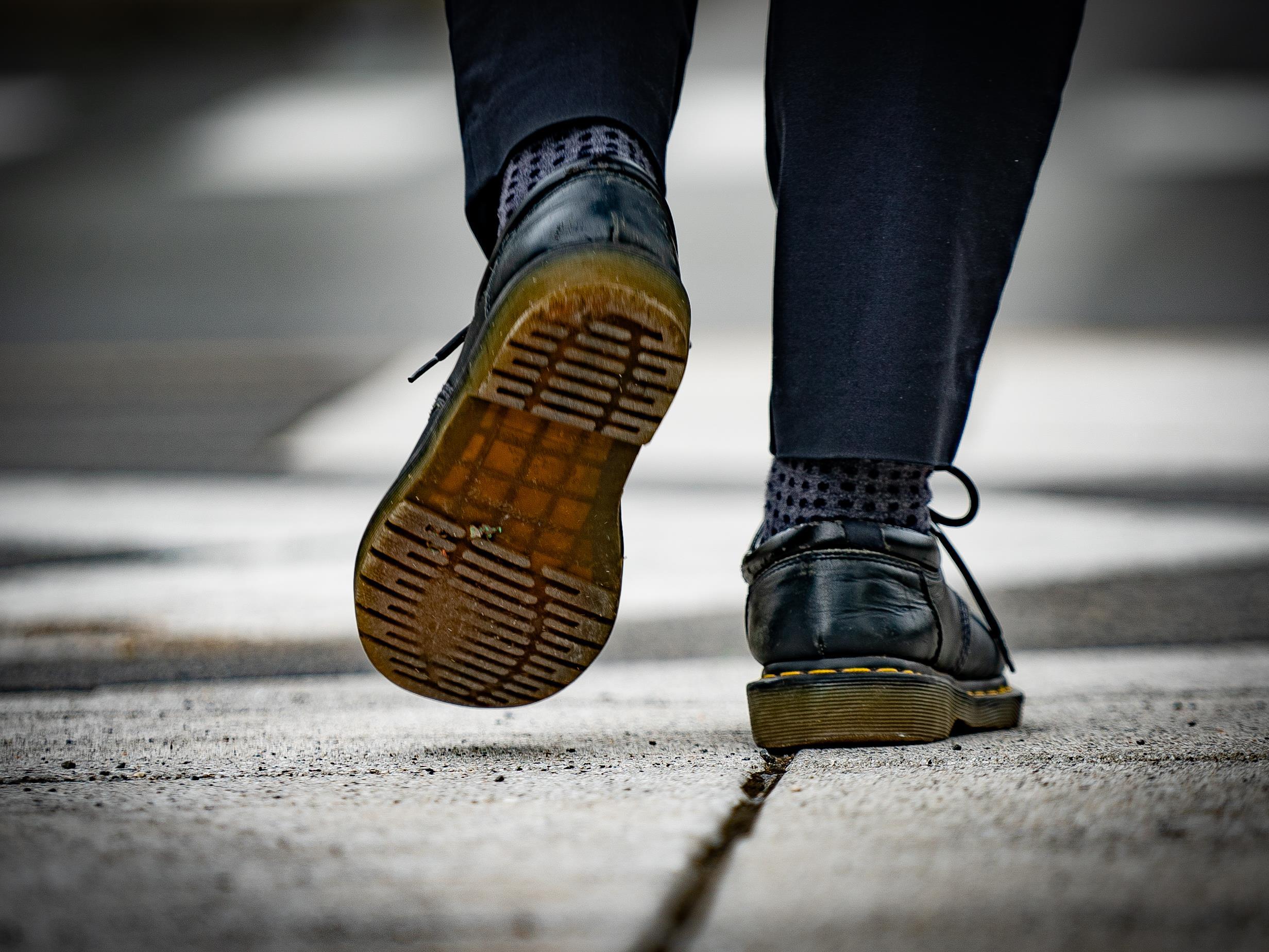 On voit en gros plan les pieds d'Adam, de derrière, qui marche sur le trottoir. Il porte des chaussures de cuir.