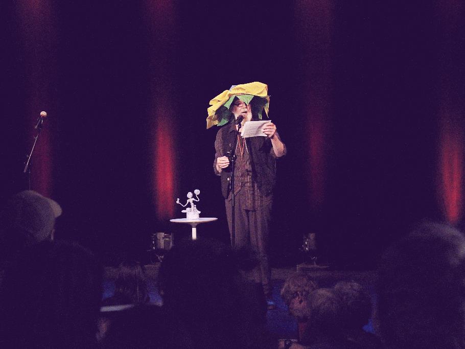 L'animateur de la soirée arborant son chapeau en fleur sur scène