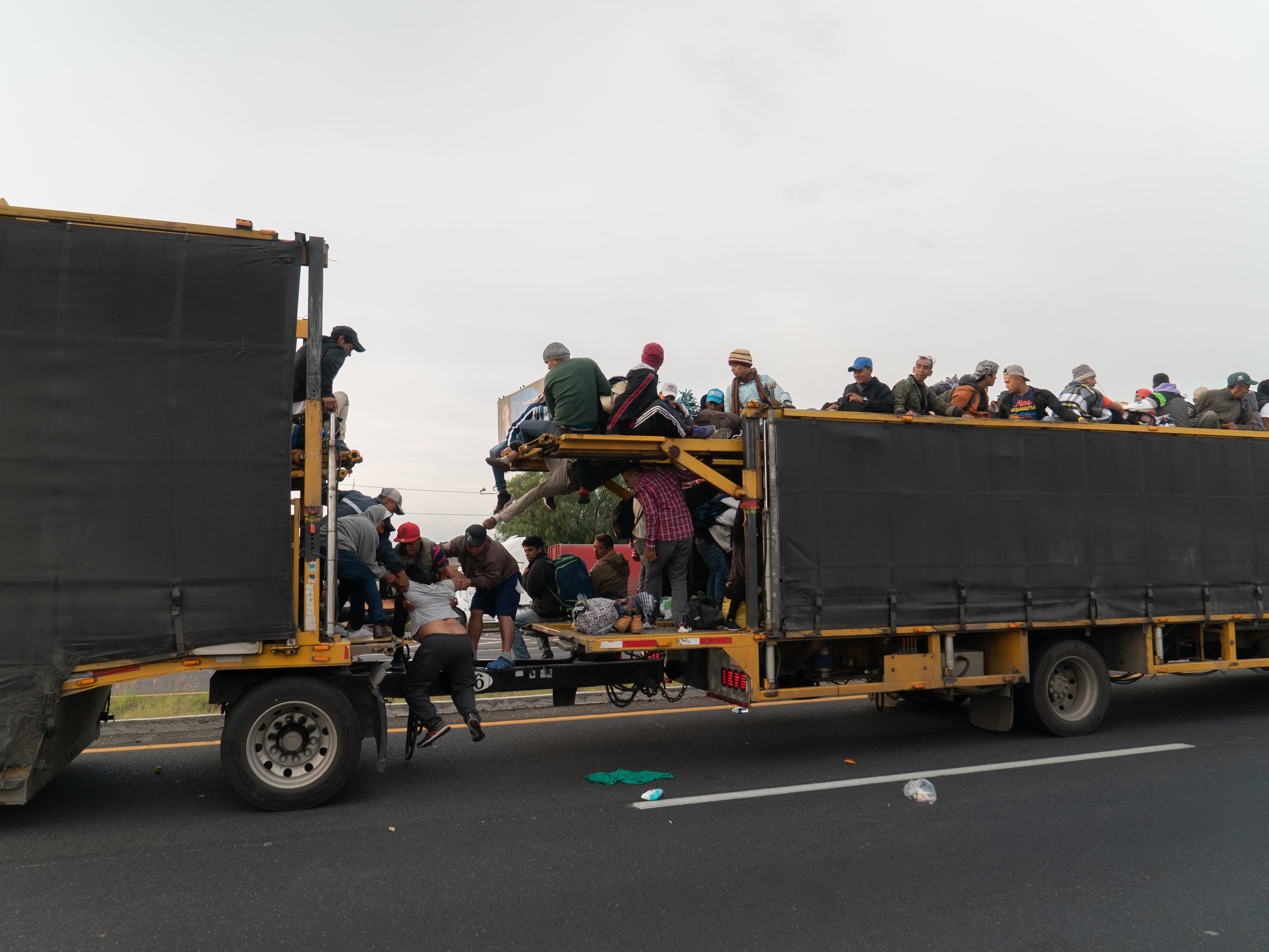 Camion avec des migrants, dont une femme qui tente de s'y hisser avec l'aide d'autres gens.