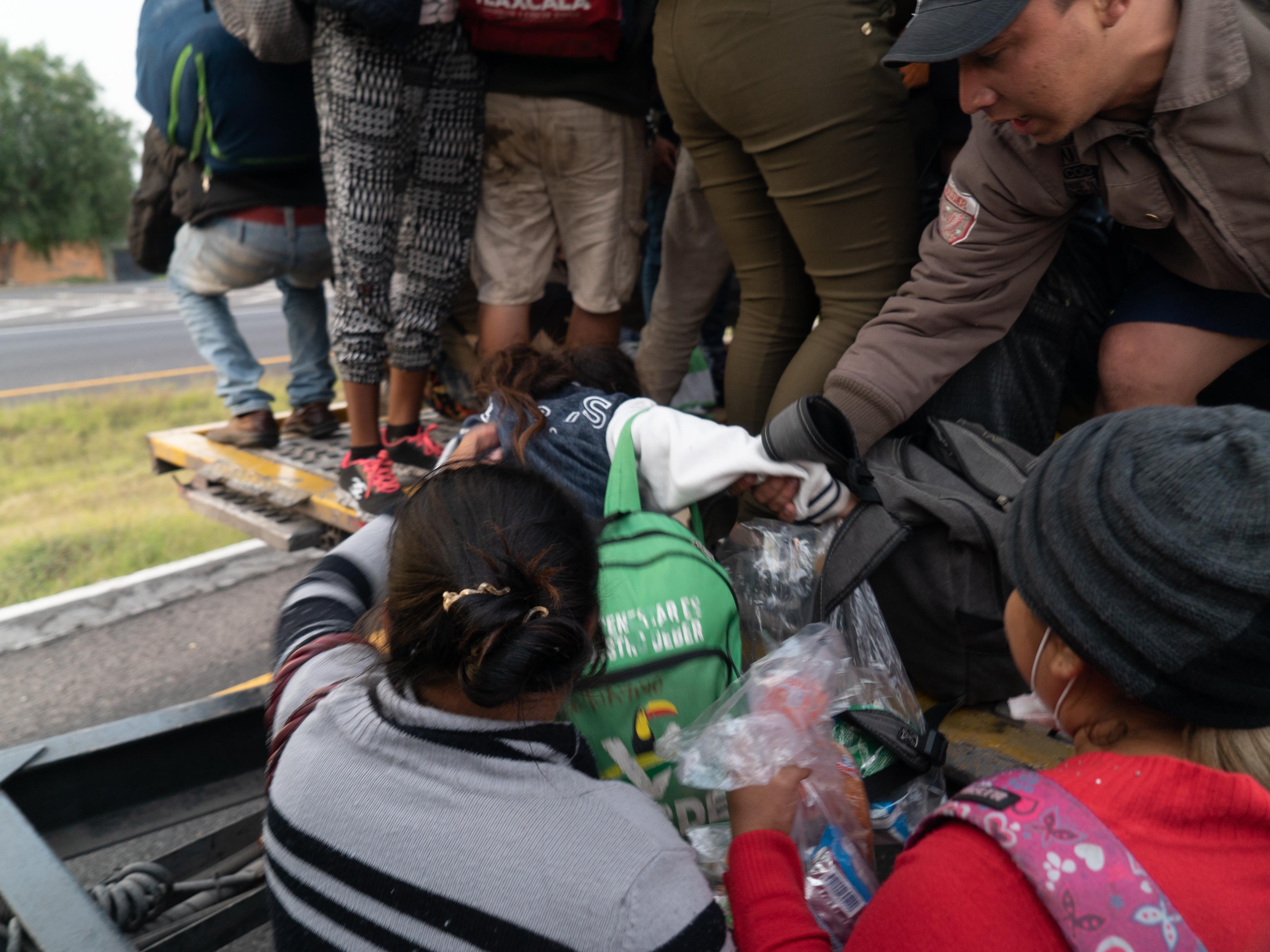 Des gens aident la fillette à grimper à bord.