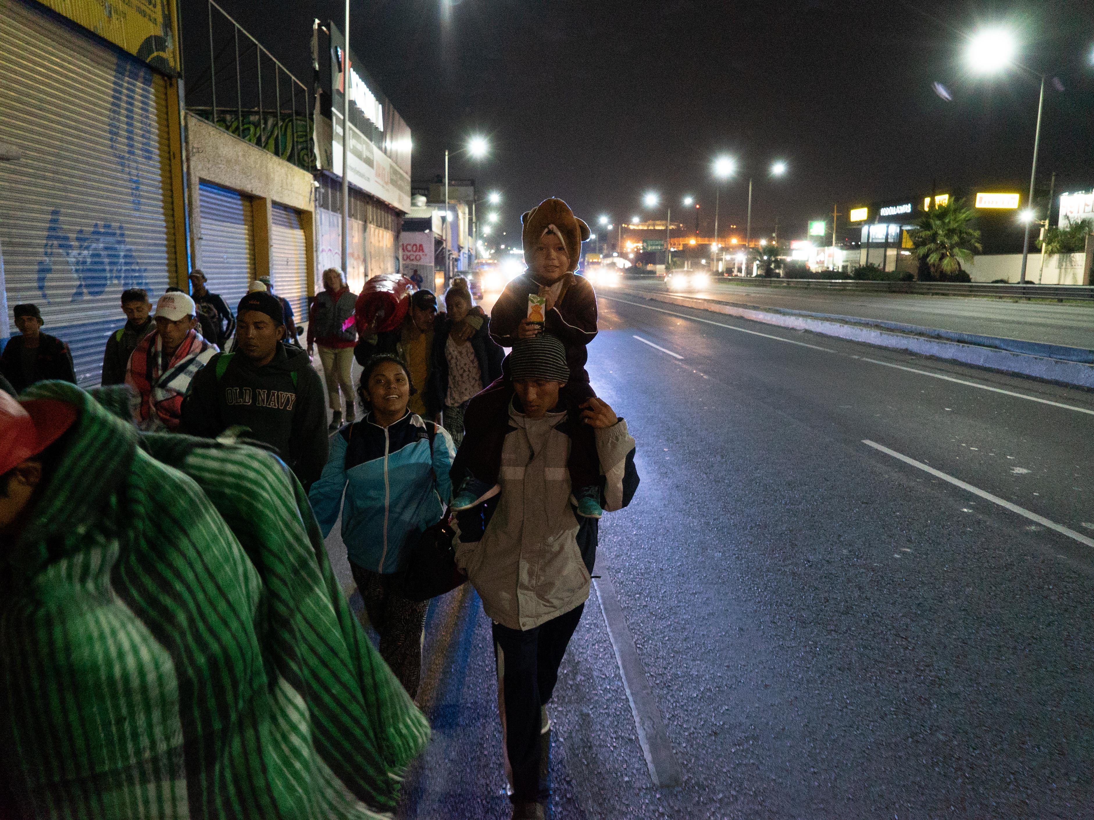 Un enfant sur les épaules de son père, qui marche avec d'autres migrants.