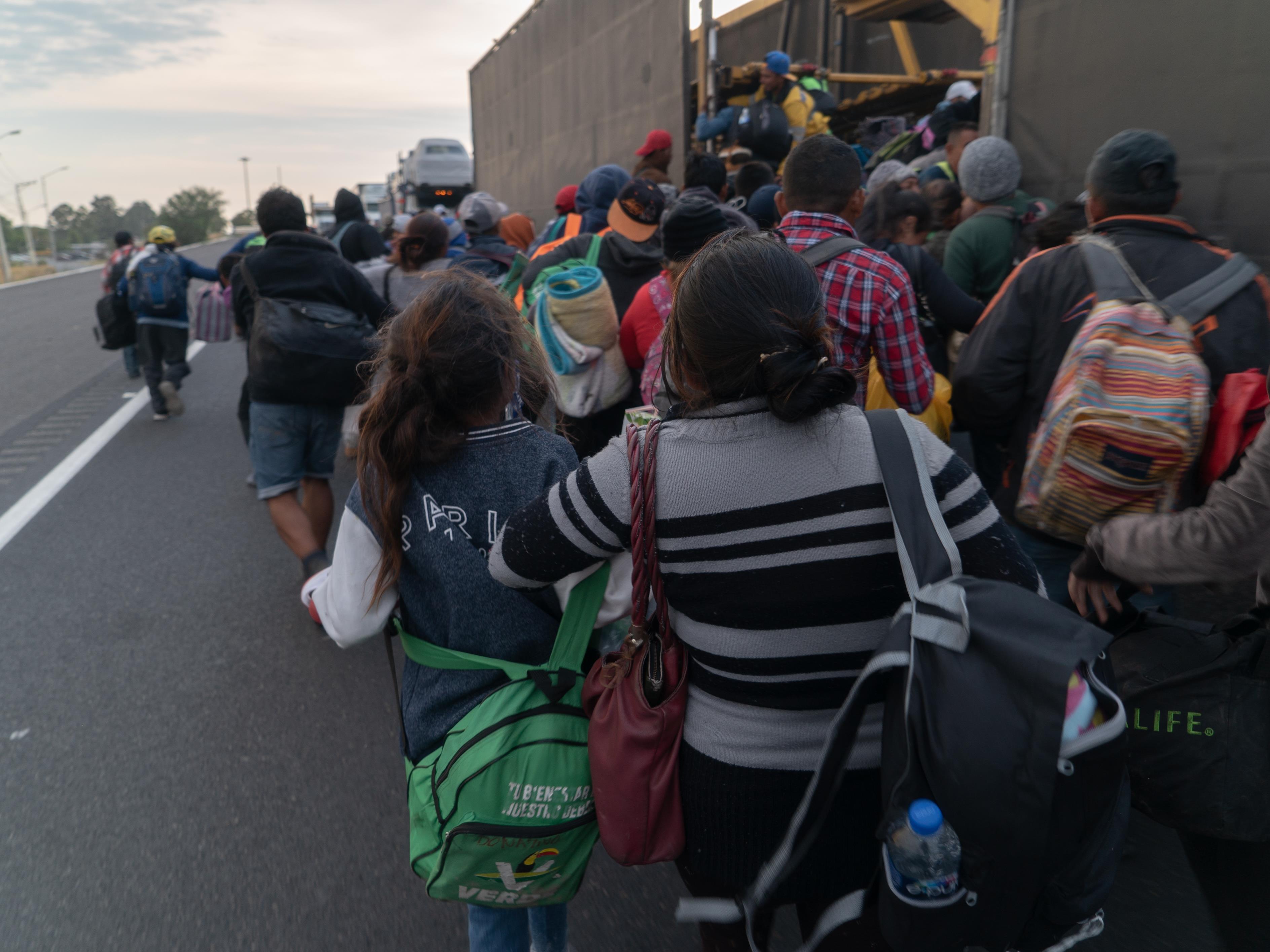 De dos, des migrants montent dans un camion.