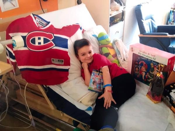 Guillaume dans son lit d'hôpital avec des jouets et un chandail du Canadien de Montréal
