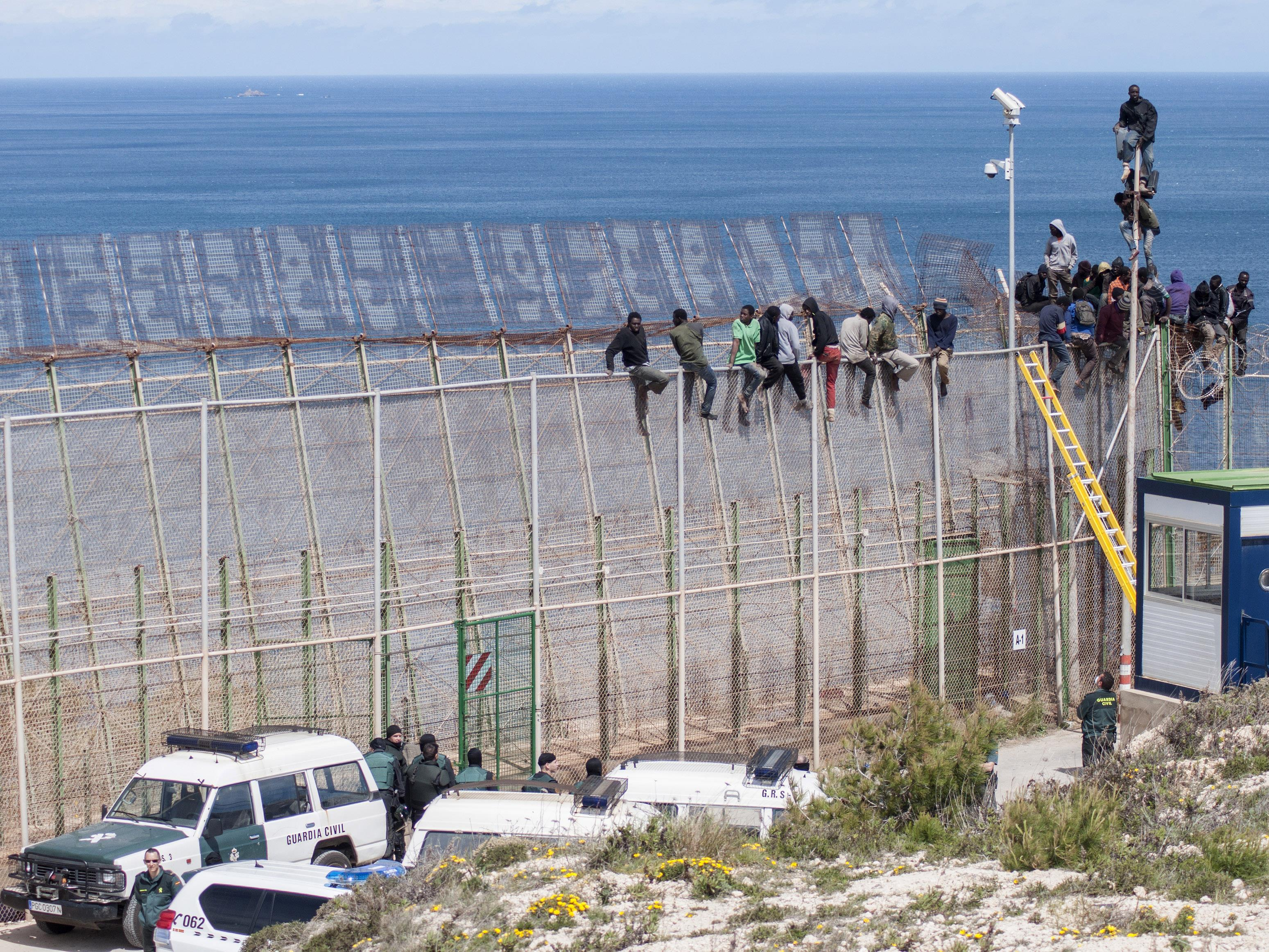 Des migrants africains tentent de franchir la frontière clôturée entre le Maroc et l'Espagne, dans l'enclave espagnole de Melilla en avril 2014.