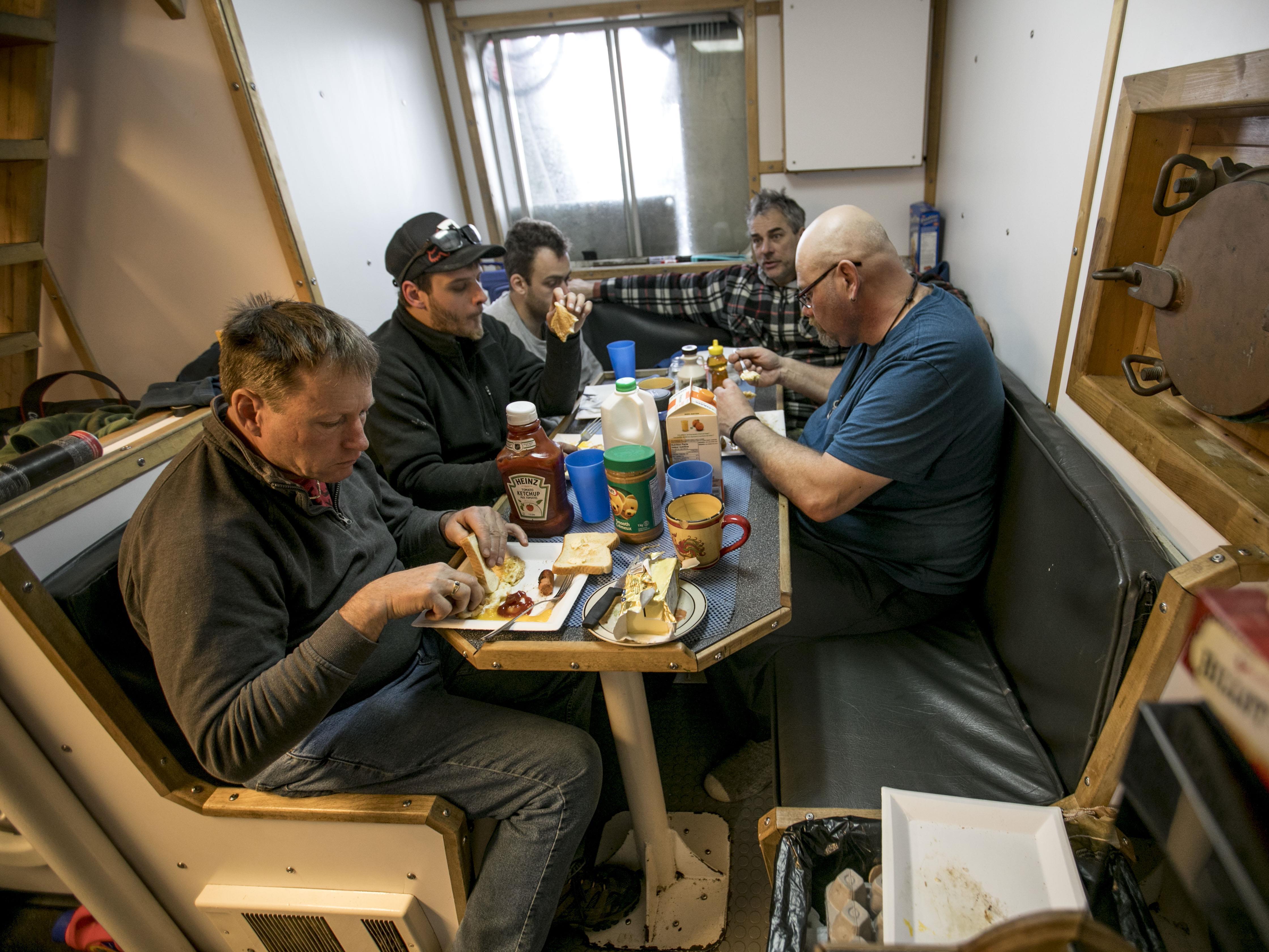Les pêcheurs mangent autour d'une table à bord du navire