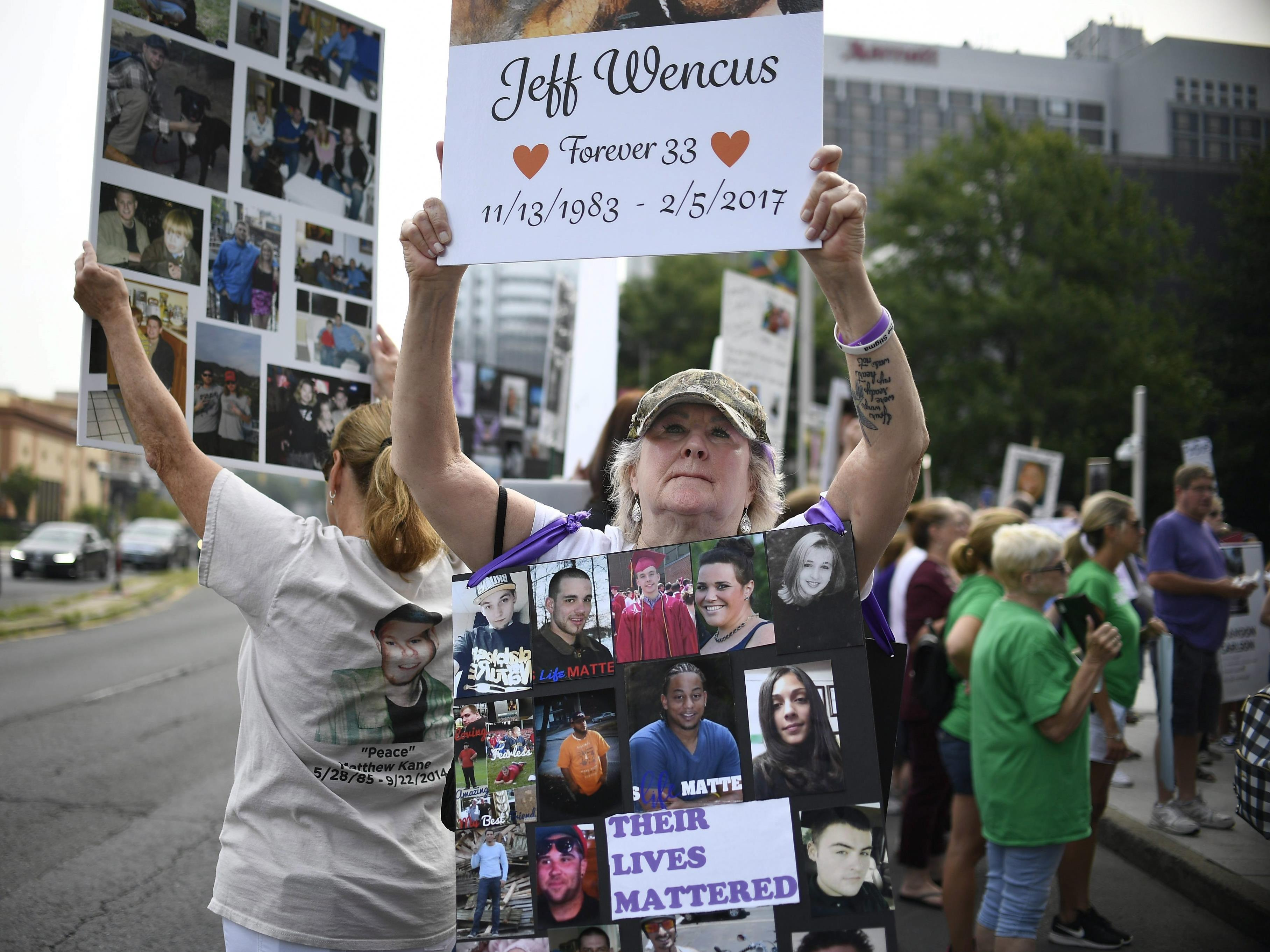 Une femme tient une affiche à la mémoire de son fils décédé.