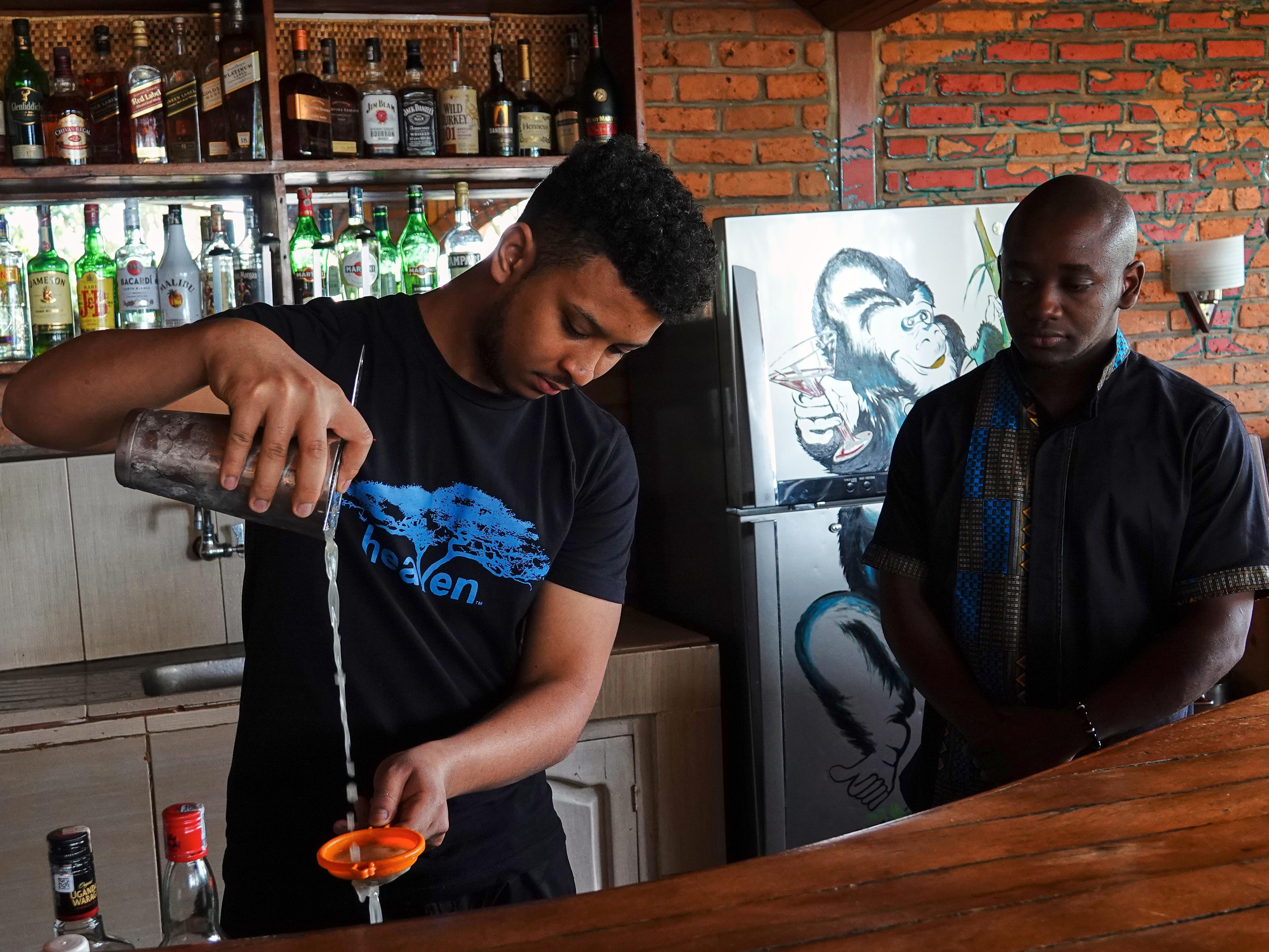 Un des barmans passe un liquide dans un tamis.