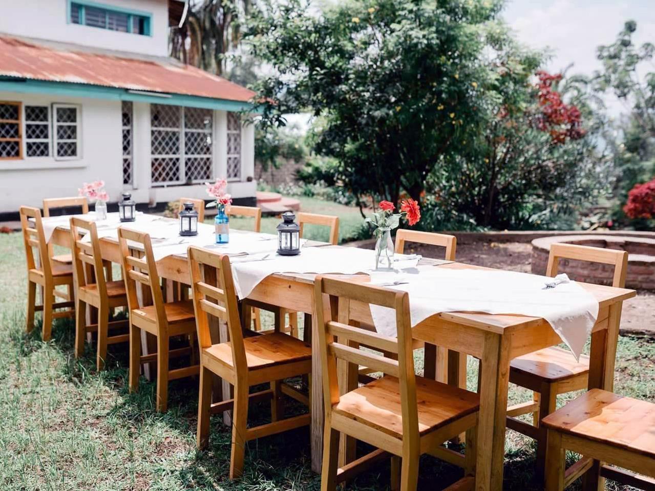 Une longue table et des chaises installées sur le parterre.