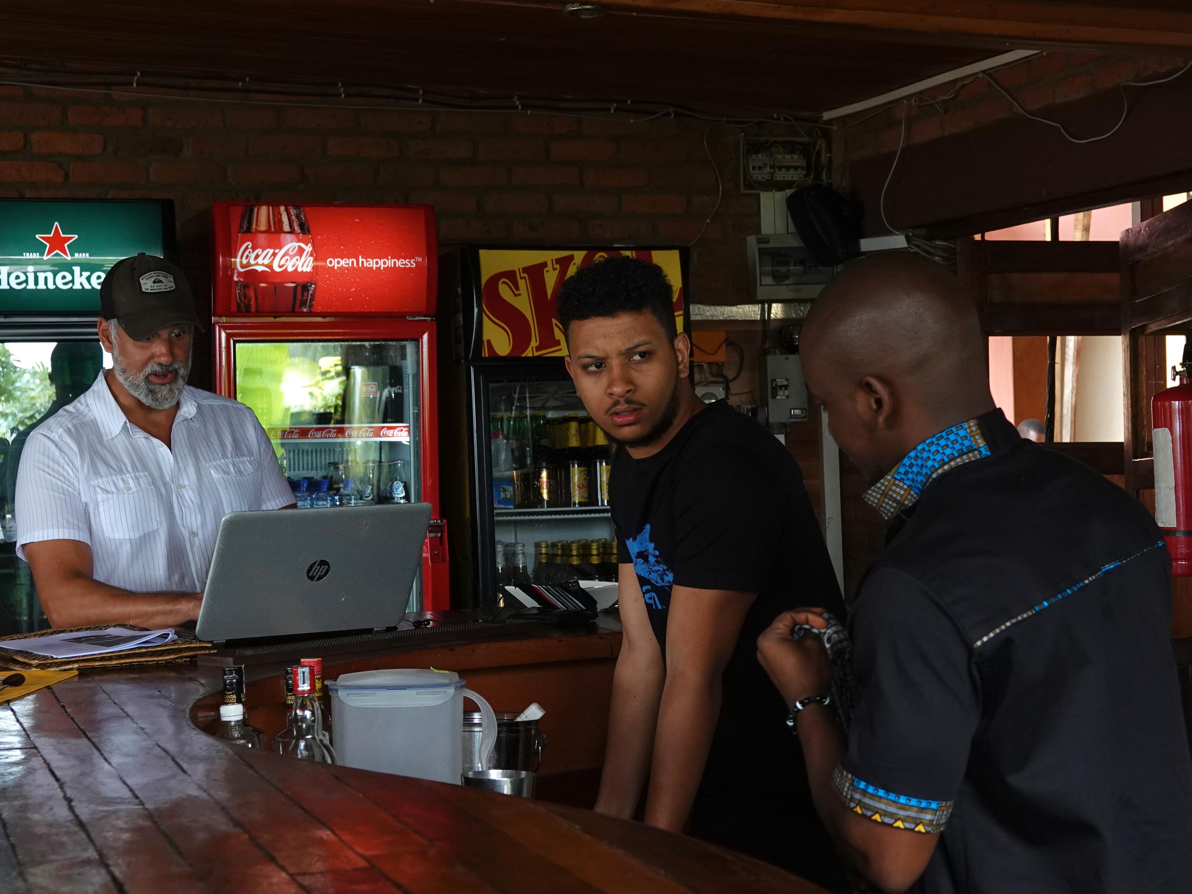 Ryan Magarian devant son ordinateur et deux serveurs derrière le bar.