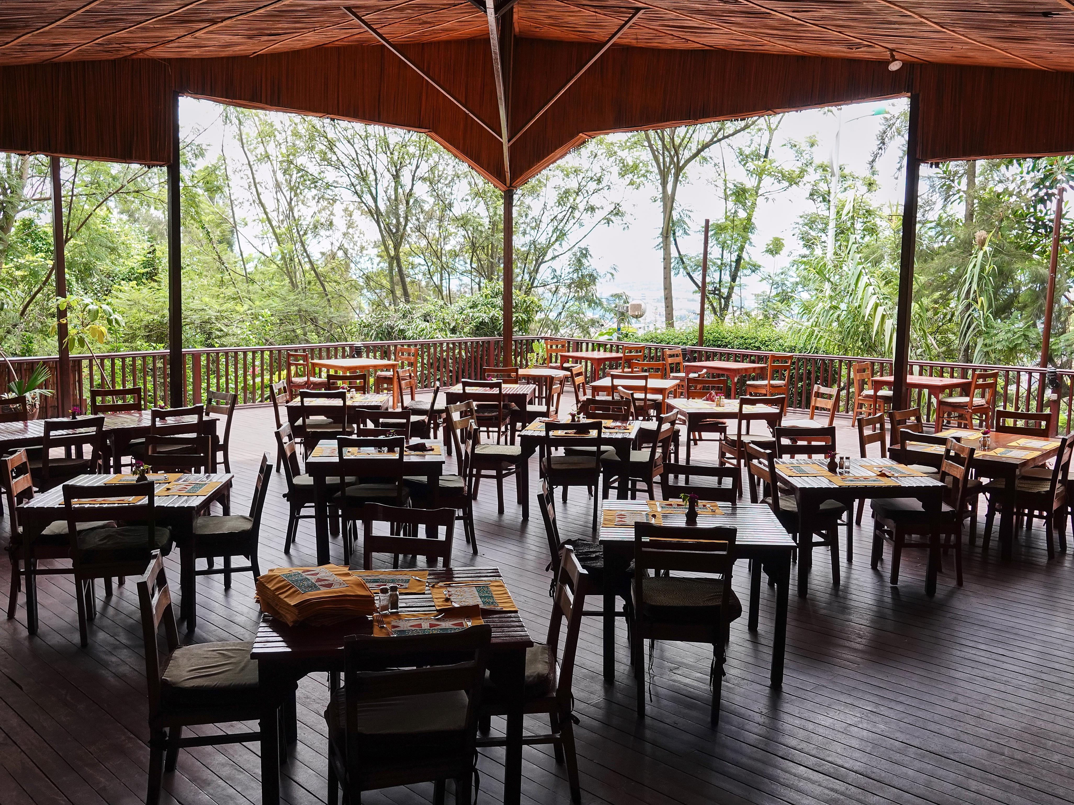 Une dizaine de tables et des chaises sur une terrasse couverte.