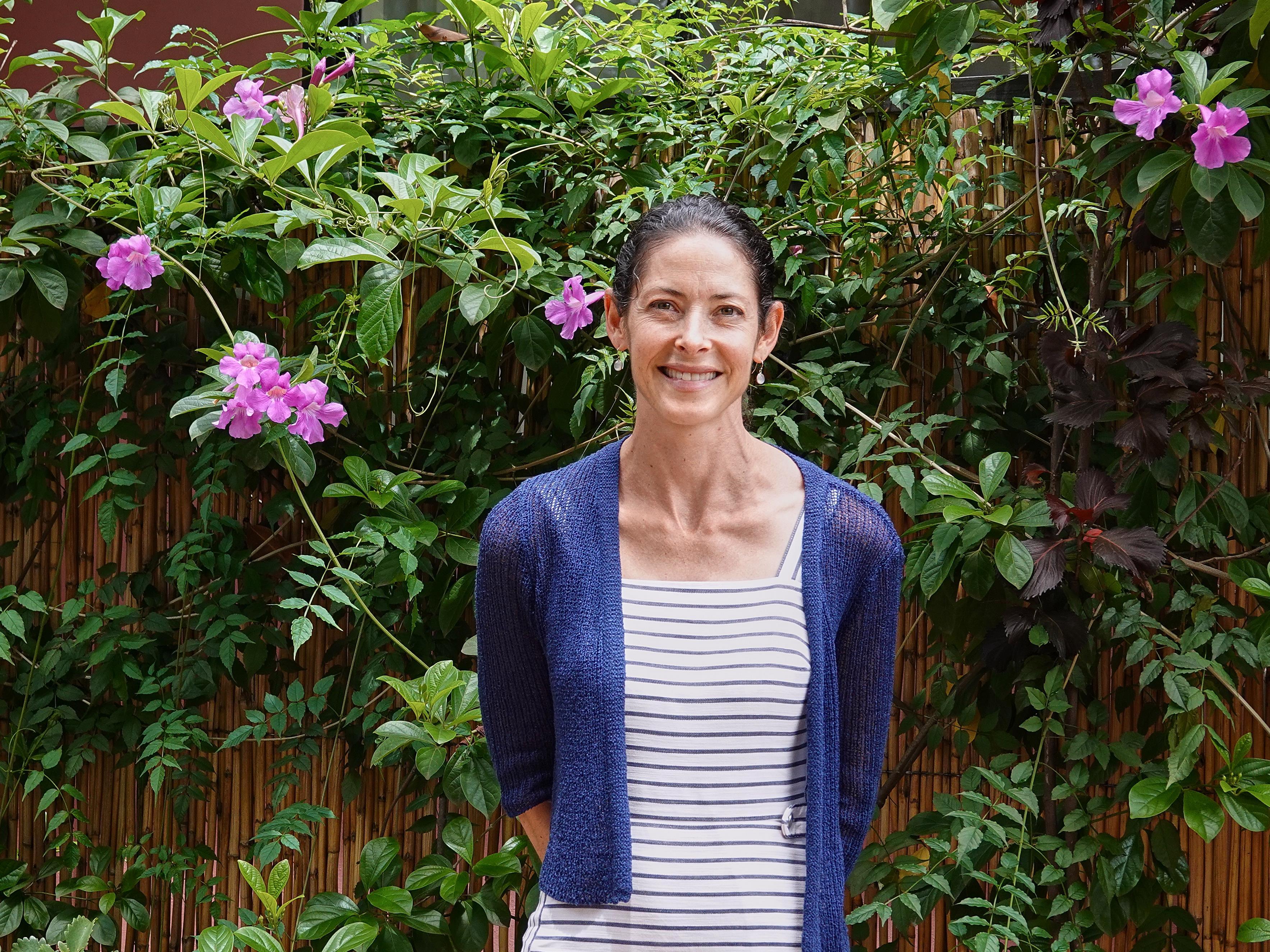Alissa Ruxin, souriante, entourée d'une végétation luxuriante.