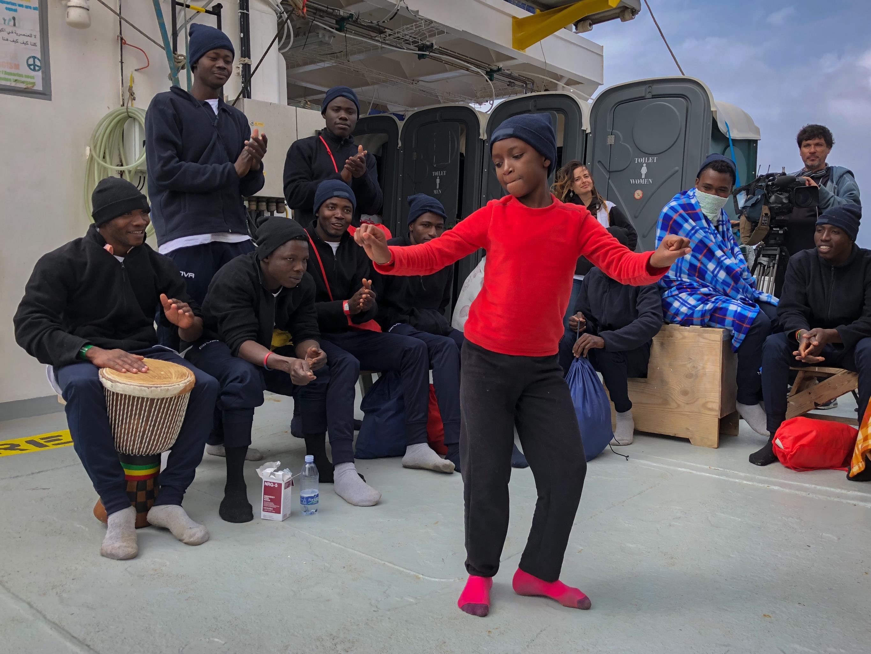 Une jeune migrante dansant au son du djembé