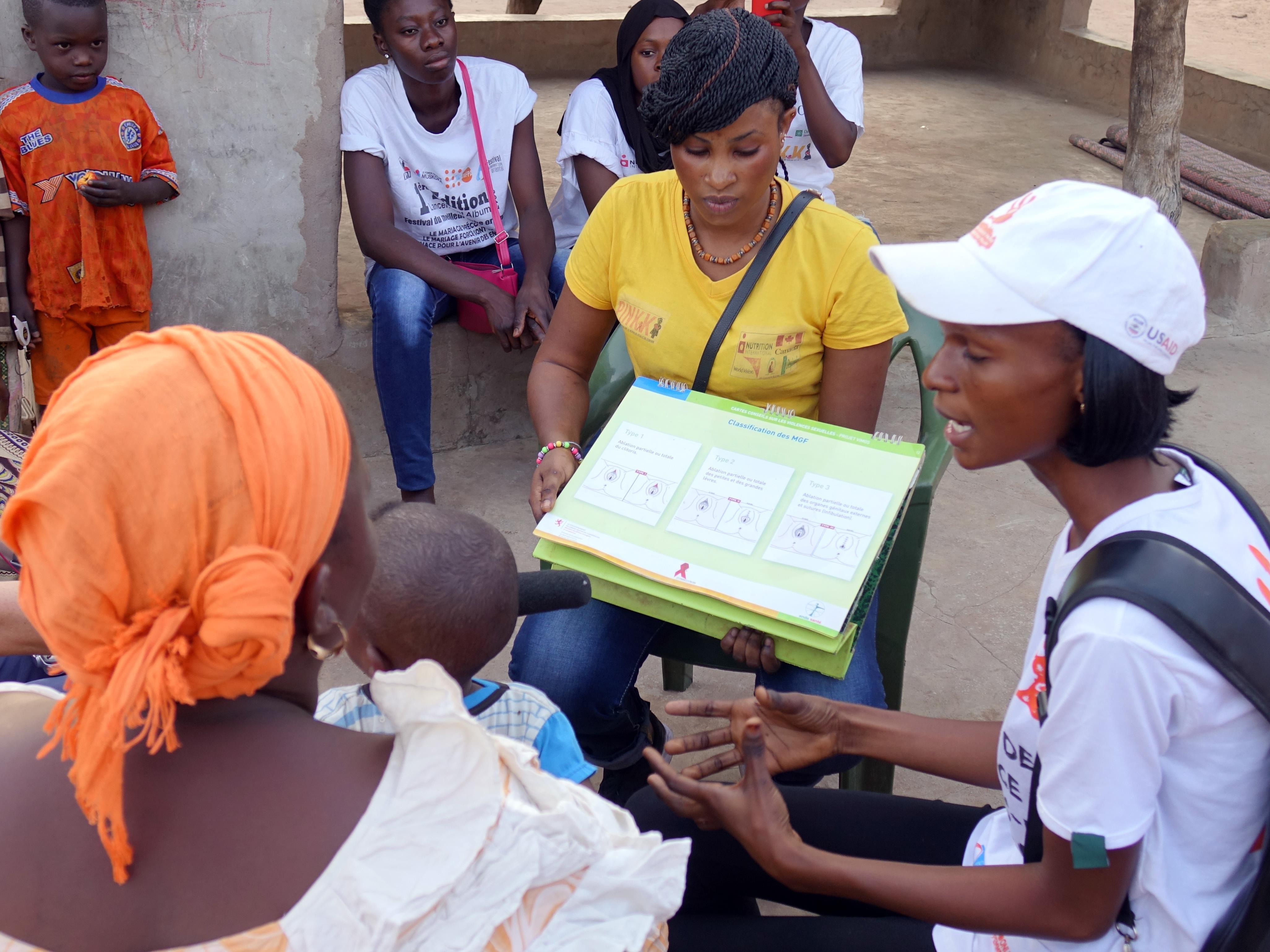Des jeunes filles discutent de l'excision avec une femme entourée de ses enfants.