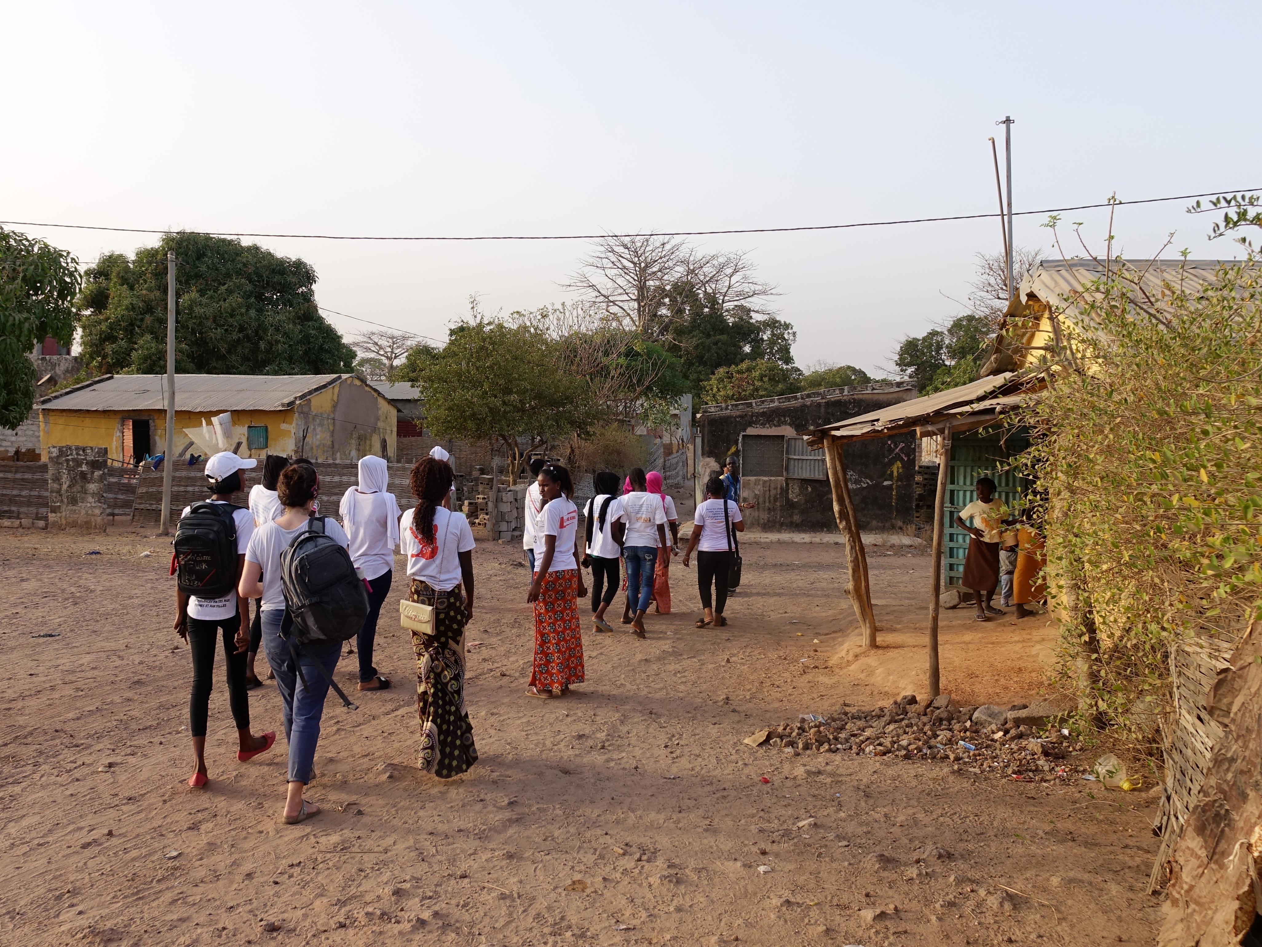 Plusieurs jeunes filles marchent sur une route de terre battue bordée de bicoques.