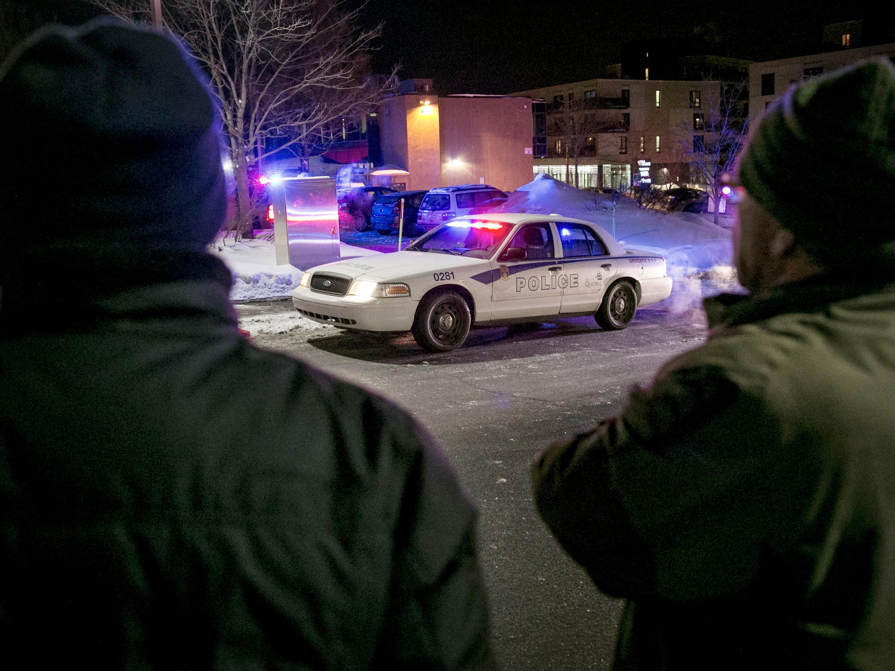 Deux hommes regardent la grande mosquée de Québec dans les instants après l'attentat