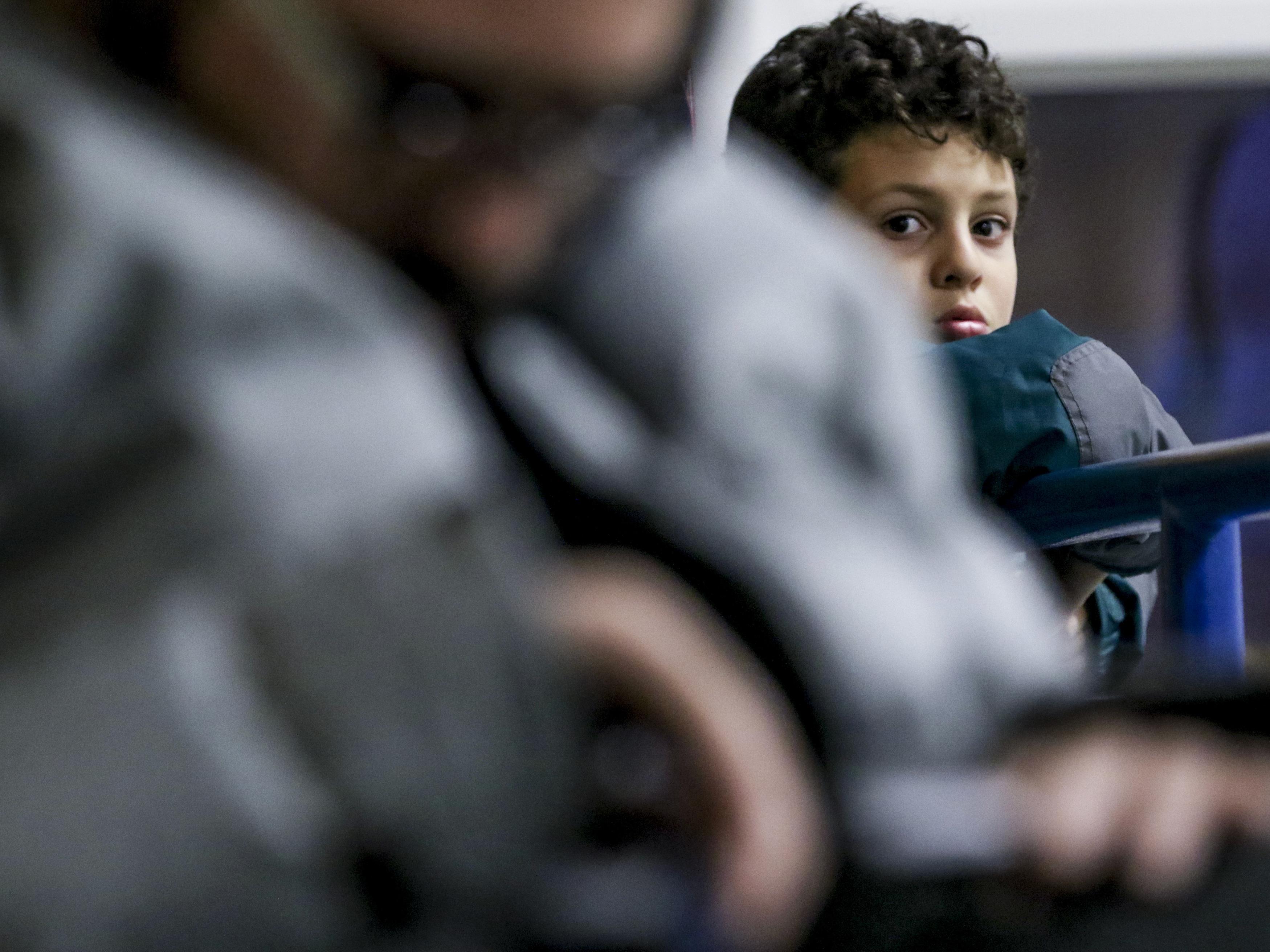 Après son match de soccer, Ayoub regarde son père de dos.