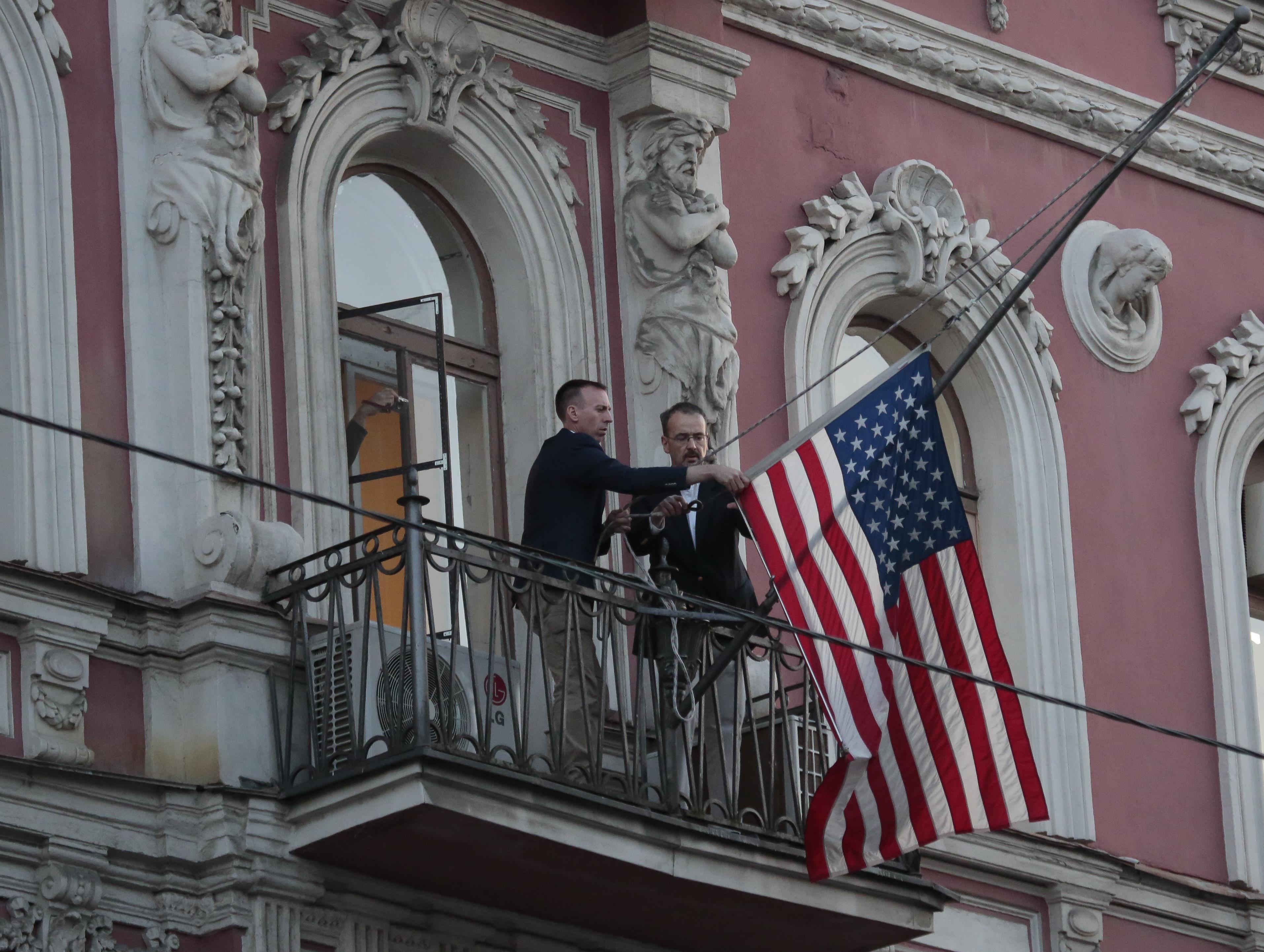 Des employés du consulat des États-Unis à Saint-Petersbourg descendent le drapeau américain de la façade de la bâtisse le 31 mars 2018.