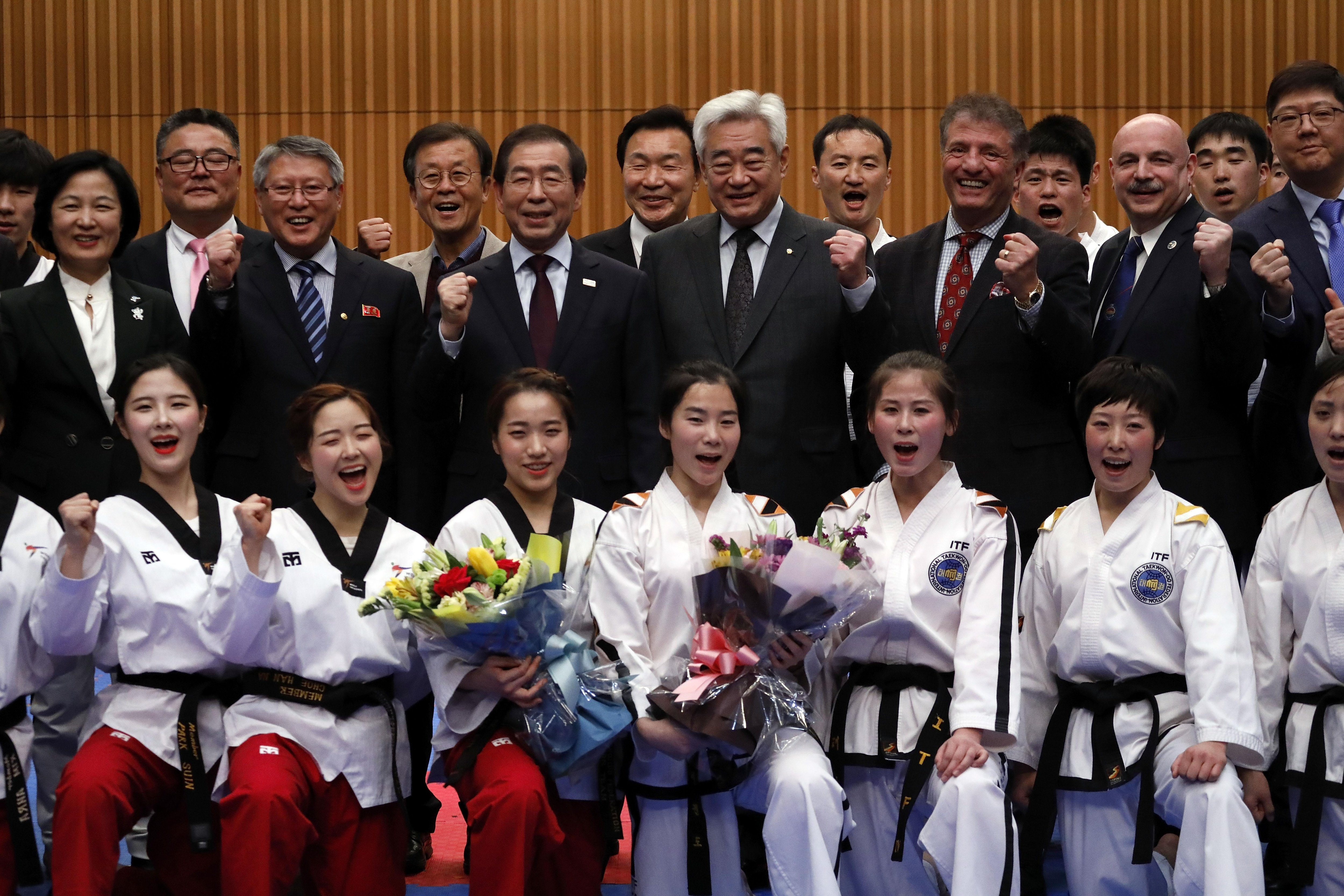 Des membres des équipes nord-coréenne et sud-coréenne posent après avoir participé à une performance de taekwondo conjointe à Séoul, le 12 février 2018, en marge des Jeux olympiques d'hiver de Pyeongchang.
